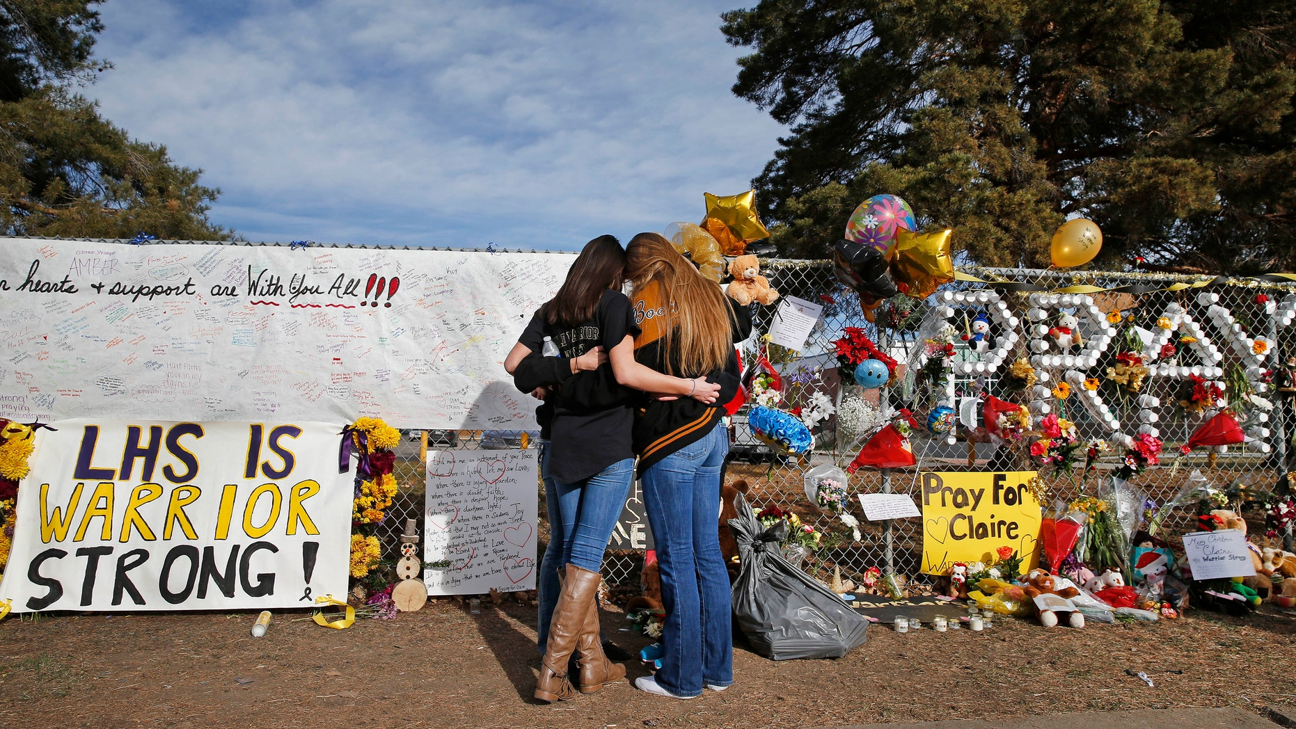 Dec. 19, 2013: In this file photo, Arapahoe High School students hug at a tribute site for fatally-wounded student Claire Davis, who was shot by classmate Karl Pierson during a school attack six days earlier at Arapahoe High School, in Centennial, Colo.
