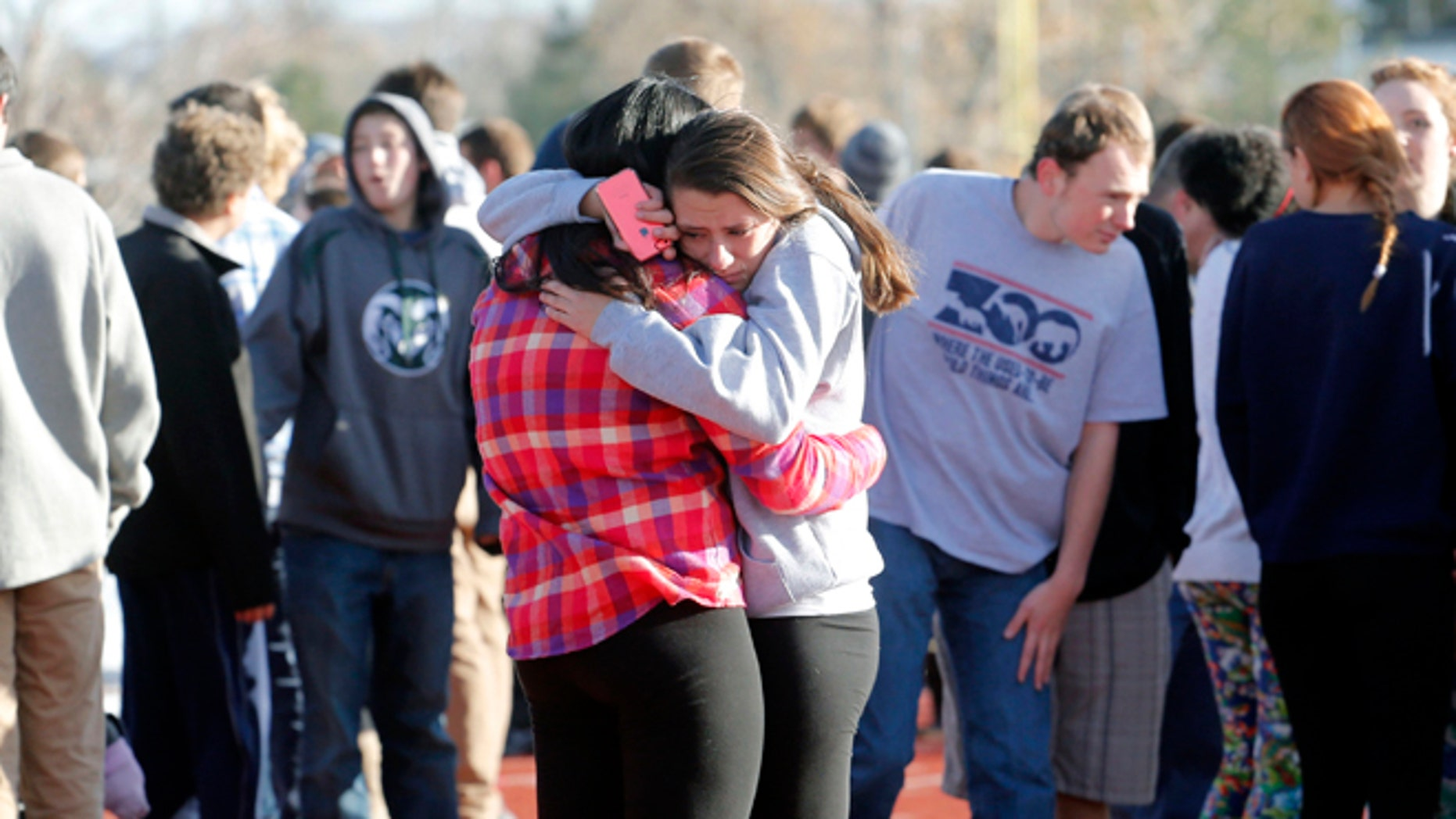 Students comfort each other at Arapahoe High School in Centennial, Colo., on Friday, Dec. 13, 2013, where a student shot at least one other student at a Colorado high school Friday before he apparently killed himself, authorities said. The shooter entered Arapahoe High School in a Denver suburb armed with a shotgun and looking for a teacher he identified by name, said Arapahoe County Sheriff Grayson Robinson. (AP Photo/Ed Andrieski)