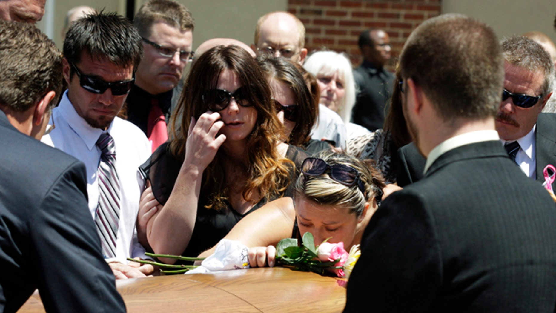 July 26, 2012: Amanda Medek, center left, looks on as her cousin Amber Vigil, center right, kisses the casket of Amanda's sister Micayla Medek, following Micayla's funeral in Denver.