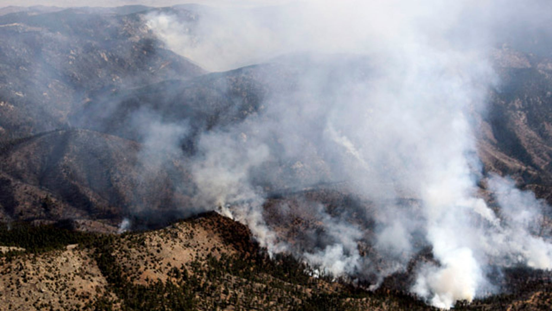 March 27: Smoke rises from the Lower North Fork Wildfire as it burns near the foothills community of Conifer, Colo