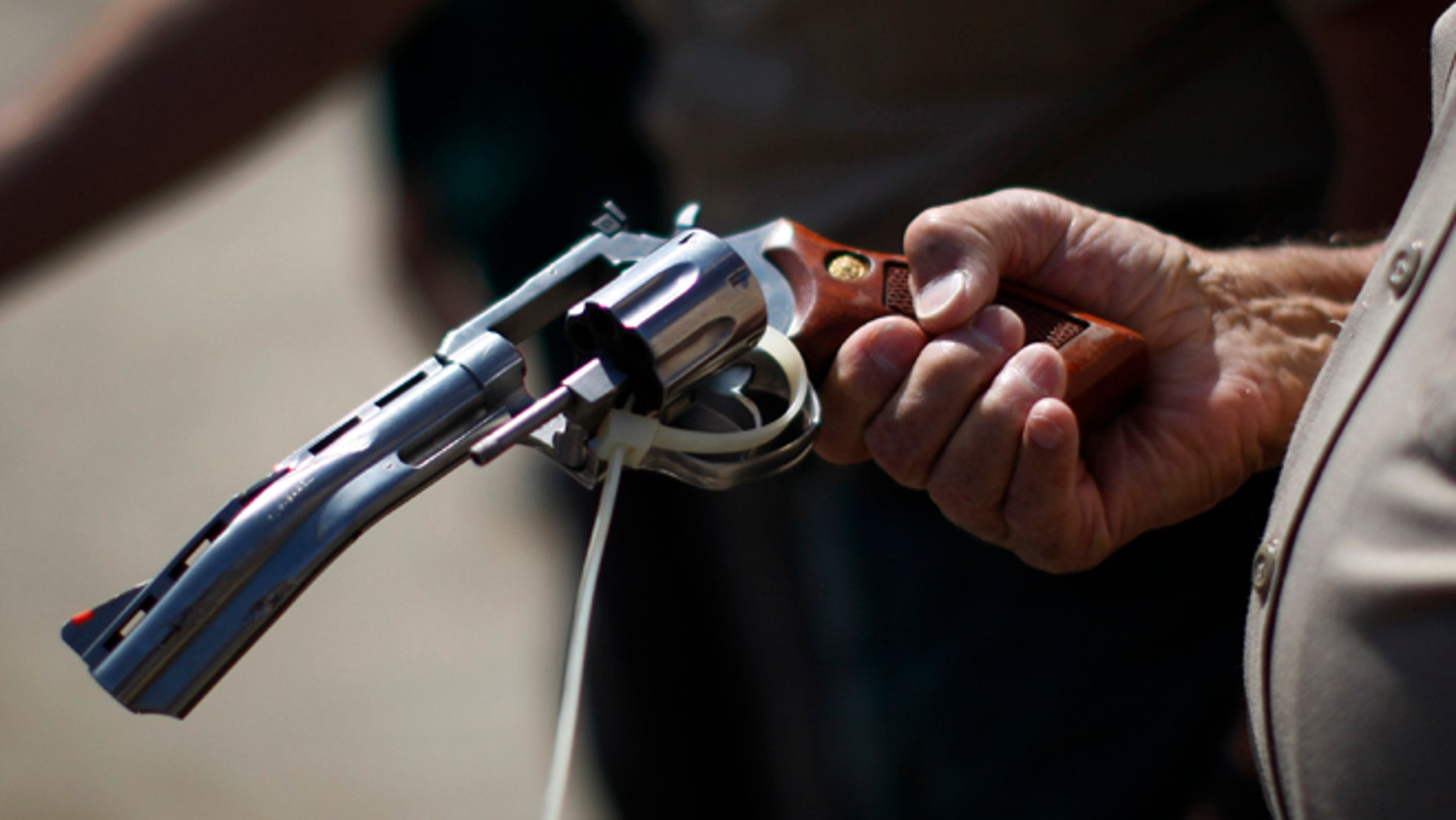 FILE: July 30, 2013: A deputy sheriff looks at a disabled gun to be melted down at  a gun buy-back program in Los Angeles, Calif.