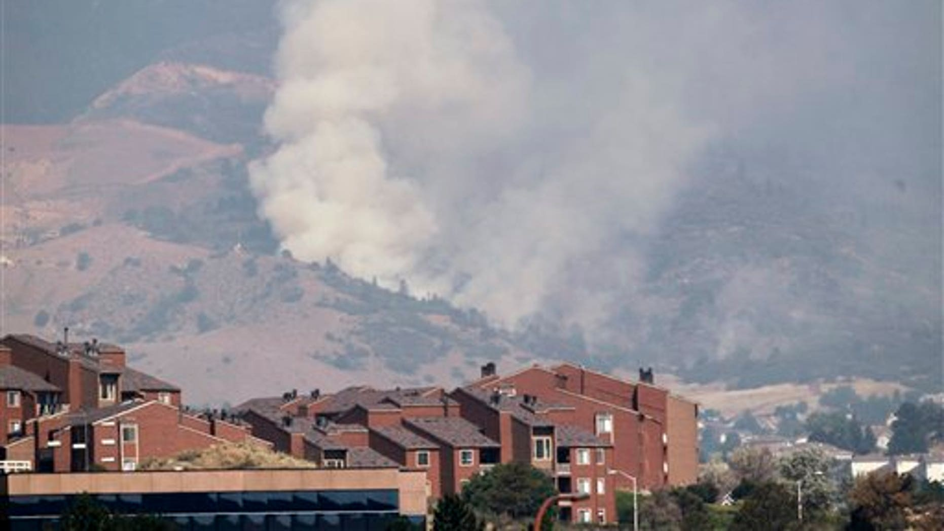 June 27, 2012: A plume of smoke rises behind homes on the Waldo Canyon wildfire west of Colorado Springs, Colo.