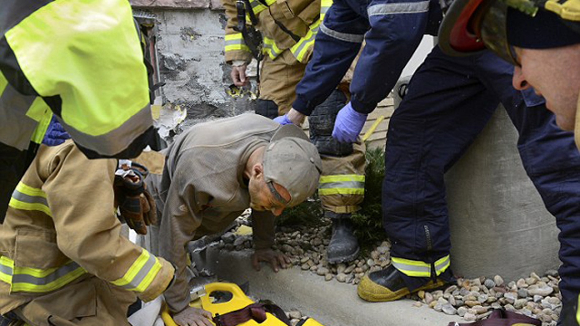 November 11, 2014: A man trapped in a wall at the rear of a Marshalls store in Longmont, Colo., crawls out of a hole and onto a backboard. Longmont Police Sgt. Matt Cage said Paul Felyk, 35, was taken to Longmont United Hospital after falling about 20 feet inside the walls and becoming trapped. (AP Photo/The Daily Times Call, Lewis Geyer)