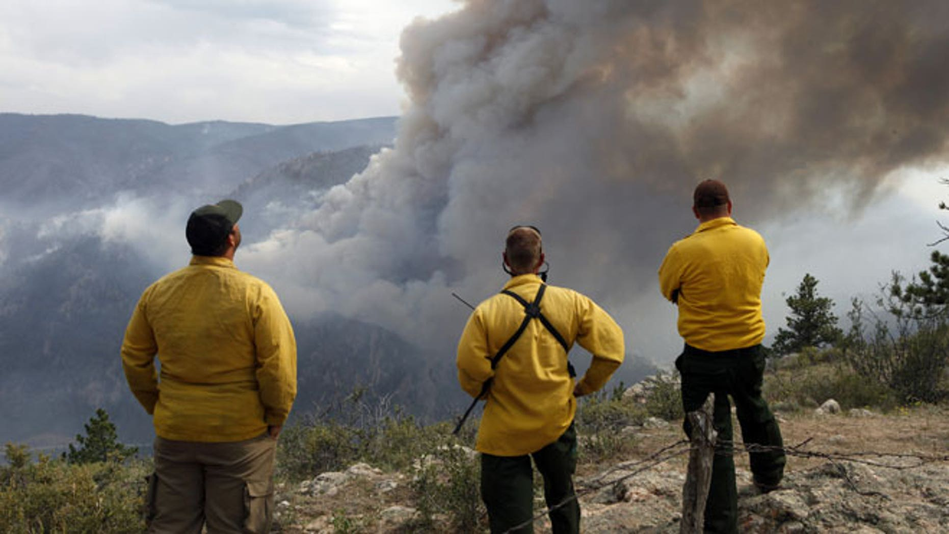 June 14, 2012: Firefighters watch as flames leap hundreds of feet in the air as the High Park wildfire fire explodes on the south side of Poudre Canyon west of Fort Collins, Colo.