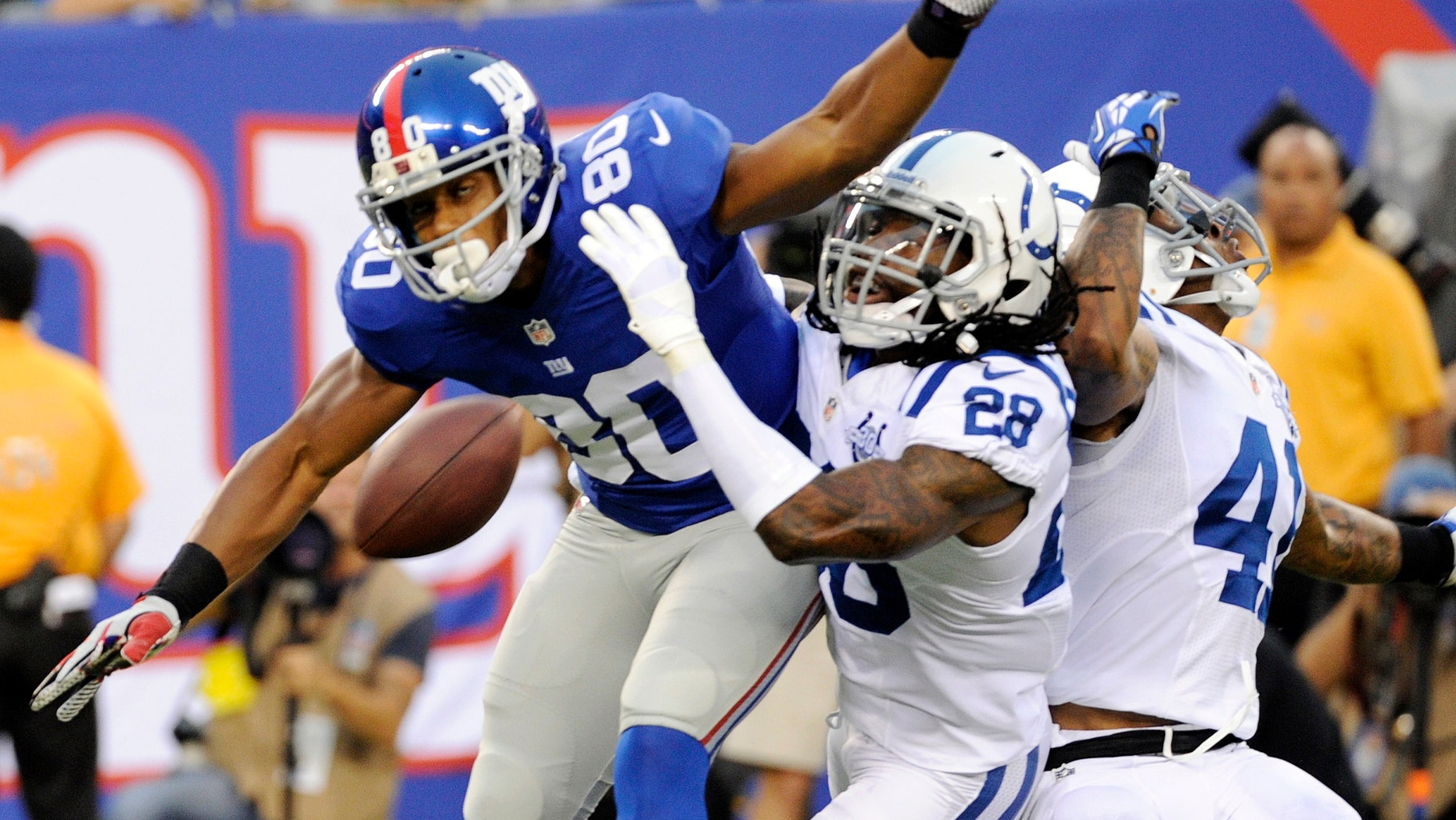 Indianapolis Colts cornerback Greg Toler (28) and Antoine Bethea (41) defend against New York Giants wide receiver Victor Cruz (80) during the first half of an NFL preseason football game on Sunday, Aug. 18, 2013, in East Rutherford, N.J. Pass interference was called on the play. (AP Photo/Bill Kostroun)