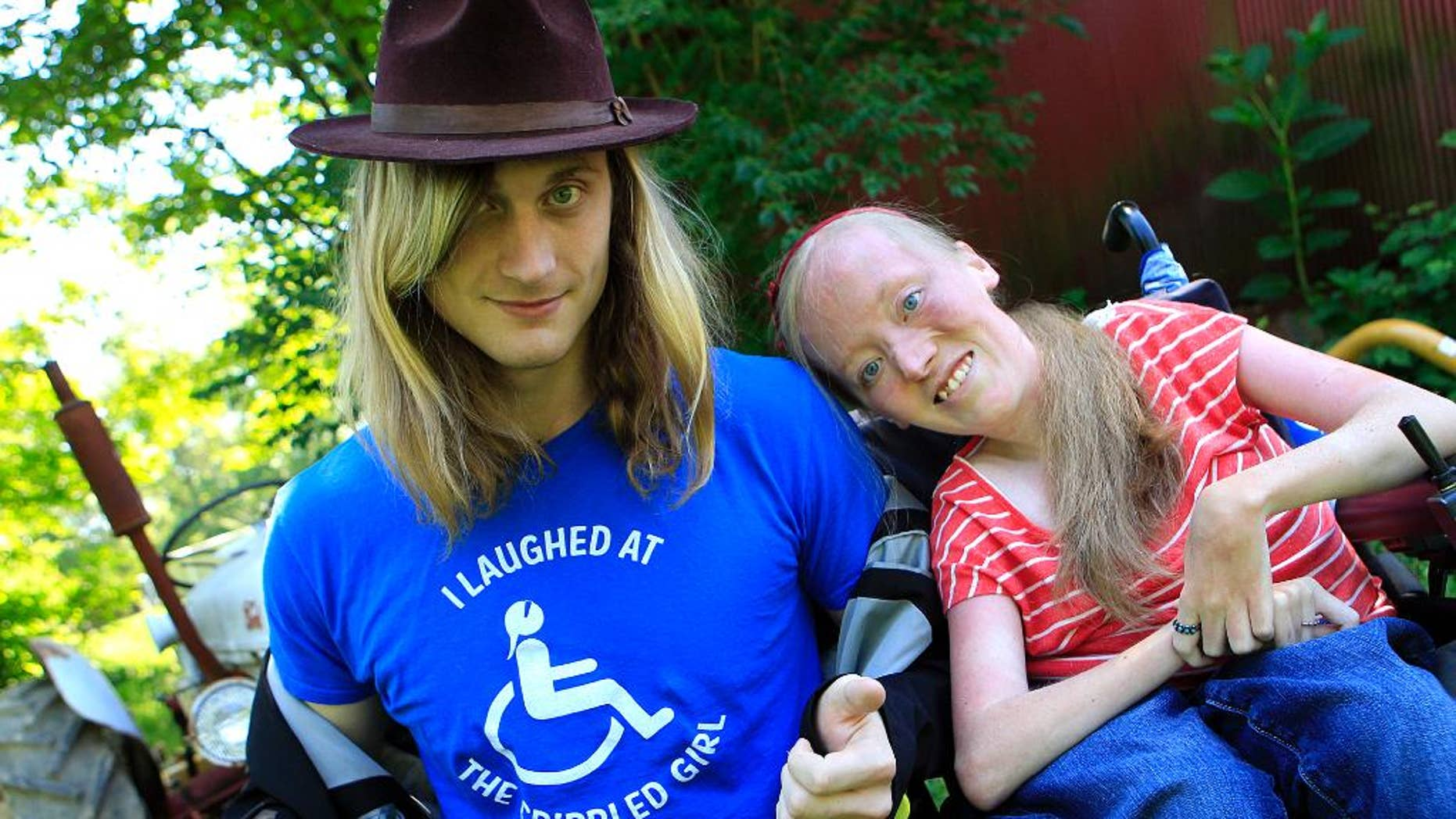 "FILE - In this June 13, 2012 file photo, Ally Bruener, right, poses for a photograph with friend Forest Thomer at her home in Alexandria, Ky. The comedy promoter, Thomer, who asked people if they wanted to laugh at a ""crippled girl"" in a wheelchair and then was arrested on a disorderly conduct charge has received $25,000 from the city to settle his federal lawsuit charging violation of his free-speech rights, the man's attorney said Wednesday, Feb. 4, 2015. The question wasn't intended to demean Bruener, but to promote her next comedy show and website. (AP Photo/The Cincinnati Enquirer, Cara Owsley, File)  MANDATORY CREDIT; NO SALES"