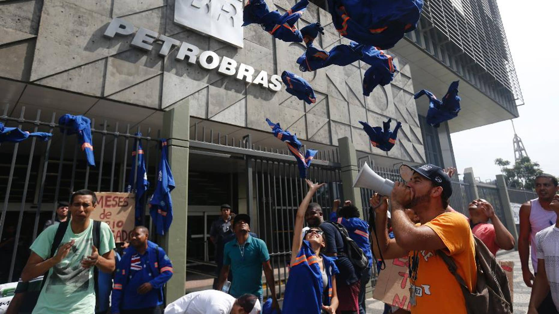 FILE - In this Feb. 4, 2015 file photo, workers whose company is contracted by Brazil's government-run oil company Petrobras throw their work uniforms at Petrobras headquarters to protest corruption, in Rio de Janeiro, Brazil. Petrobras was accused by federal prosecutors of the biggest corruption scheme in Brazil's history in 2014, in allegations that at least $2 billion in bribes were paid out over about a decade. Several top officers resigned and even pulled leading politicians into ongoing investigations. (AP Photo/Silvia Izquierdo, File)