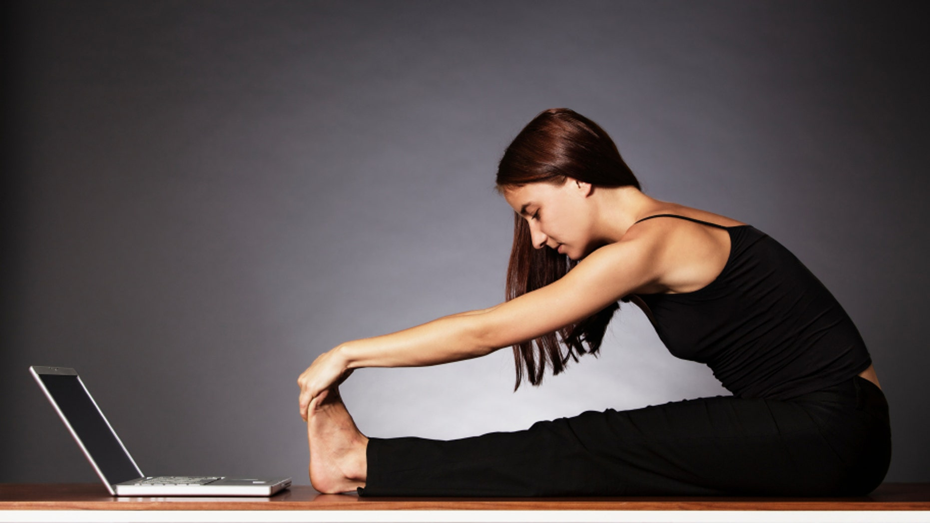 Balance at work: Young pretty woman in black sitting in front of laptop and stretching her legs .