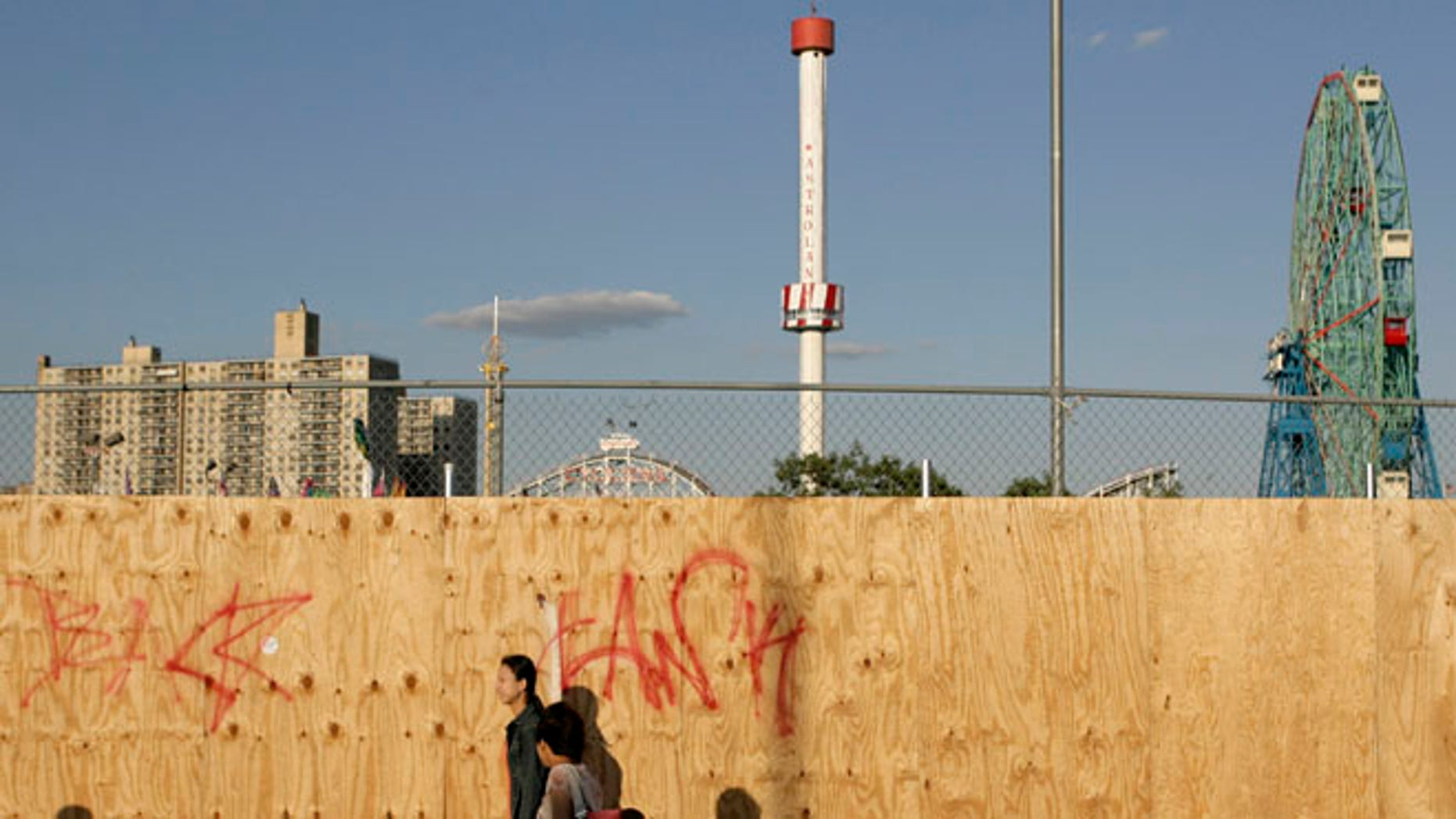 June 6, 2007: In this file photo, pedestrians walk past a boarded up section of the Coney Island amusement district in the Brooklyn borough of New York with the Astrotower rising in the background.