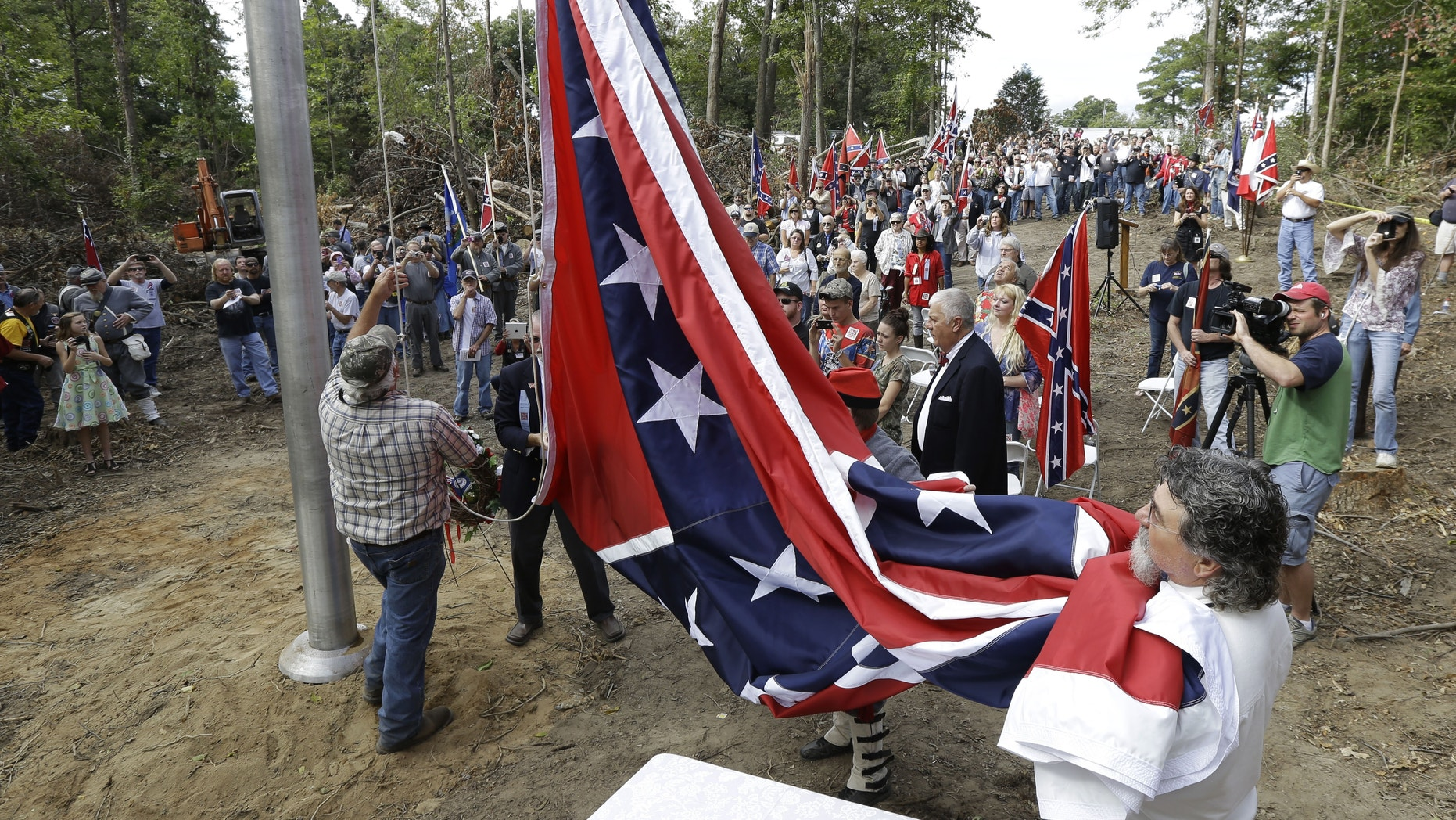 "A group called ""Virginia Flaggers"" raise the Confederate battle flag on a pole near Interstate 95 in Chester, Va., Saturday, Sept. 28, 2013.  Hundreds gathered Saturday in freshly cleared woods along Interstate 95 to celebrate the raising of a Confederate battle flag, an event that stirred strong feelings among those who view it as a symbol of division.  (AP Photo/Steve Helber)"