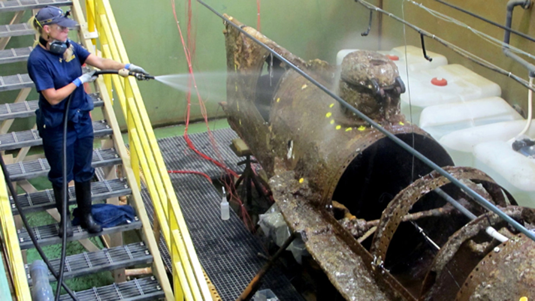 August 12, 2014: Conservator Lisa Nasanen uses a hose to wet down the hull of the Confederate submarine H.L. Hunley at the Warren Lasch Conservation Center in North Charleston, S.C. After the submarine sat in a chemical bath for more than three months to help loosen the encrustation, scientists on Tuesday began the laborious job of removing the built-up sediment by hand. The work is expected to take between eight months and a year and scientists hope that when the hull is revealed, it will provide the final clues as to why the hand-cranked sub, the first in history to sink an enemy warship, sank off South Carolina in 1864.  (AP Photo/Bruce Smith)