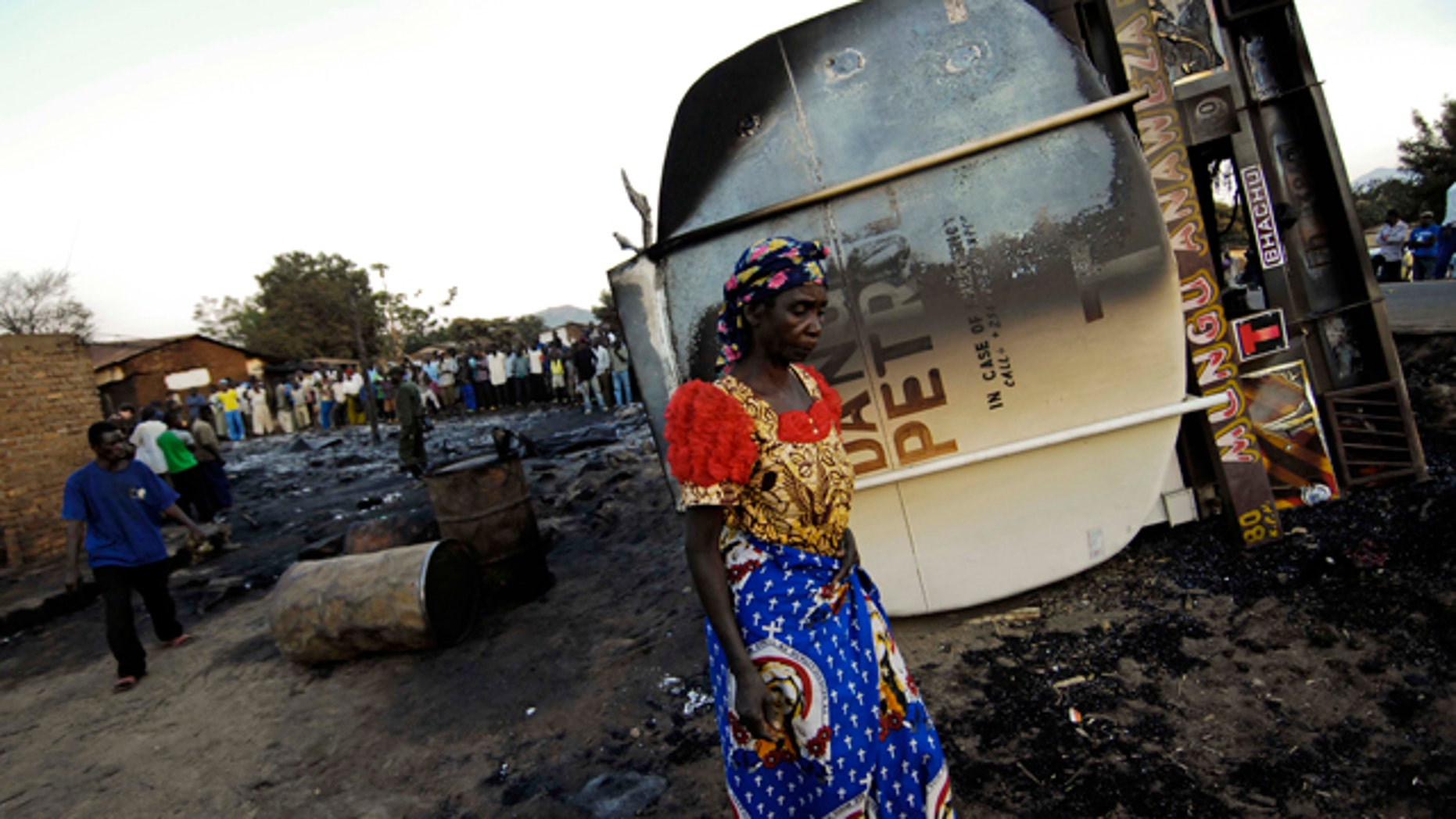 July 3: An inhabitant of the town of Sange, eastern Congo, walks past the burned out wreckage of a tanker truck involved in a accident Friday night.