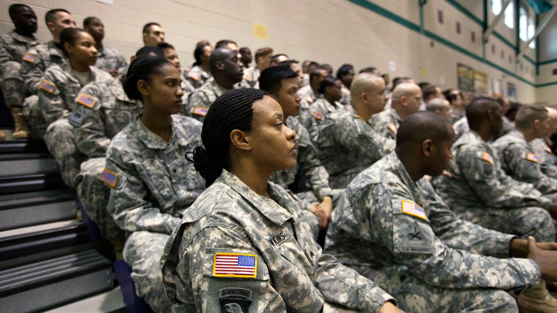 U.S. Army Sgt Dawn Hawkins, foreground, listens to Secretary of Defense Chuck Hagel speak to soldiers about the Army's future during a visit to Fort Eustis, Va., Tuesday, Feb. 25, 2014. Hagel is proposing to shrink the Army to its smallest size in three-quarters of a century, hoping to reshape the military after more than a decade of war in Iraq and Afghanistan and roped in by fiscal constraints set by Congress. (AP Photo/The Virginian-Pilot, The' N. Pham)  MAGS OUT