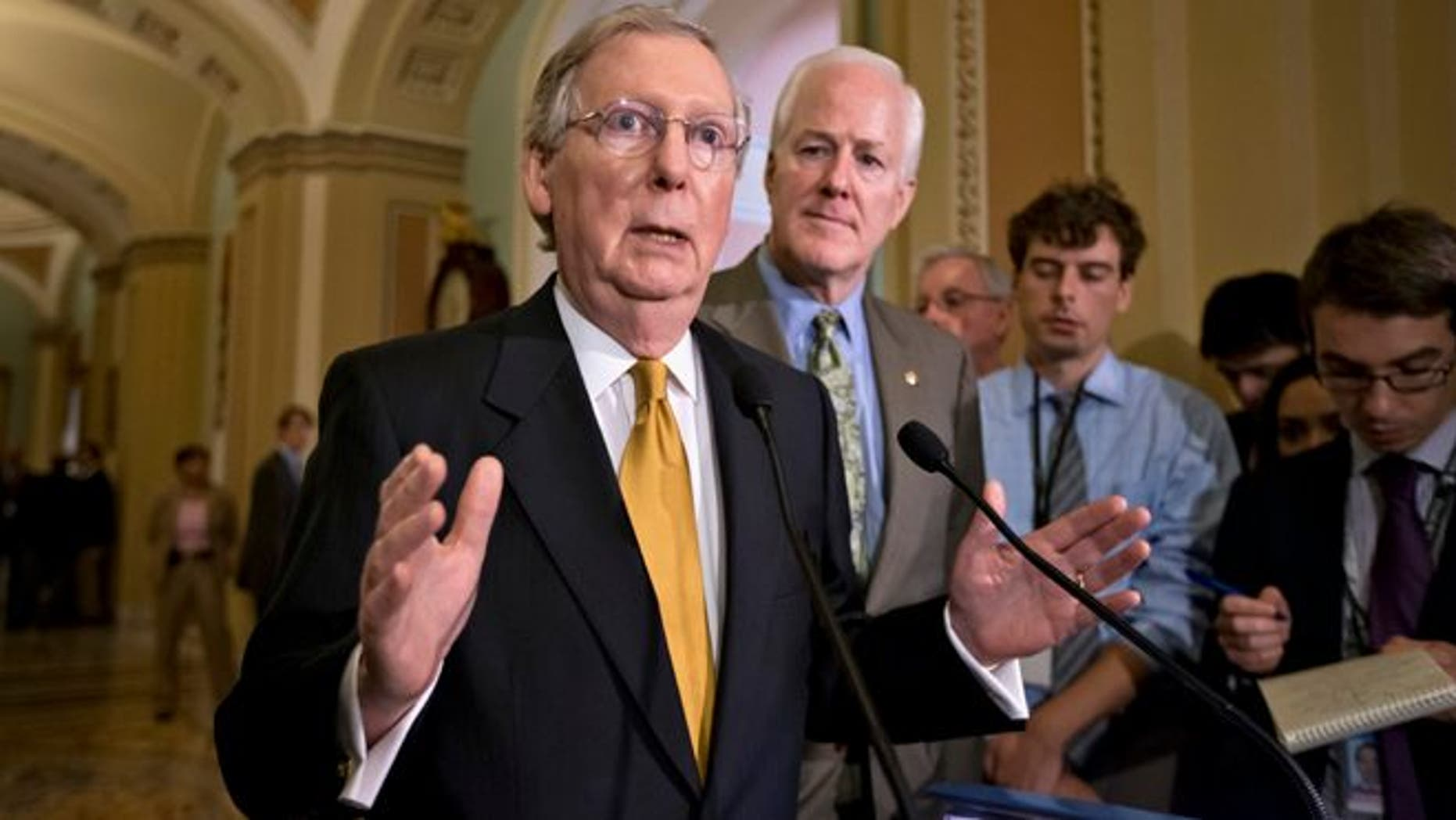 Senate Minority Leader Mitch McConnell of Ky., left, accompanied by Senate Minority Whip John Cornyn of Texas, gestures as he speaks with reporters on immigration, intelligence leaks and other issues following a Republican strategy session on Capitol Hill in Washington, Tuesday, June 11, 2013.  (AP Photo/J. Scott Applewhite)