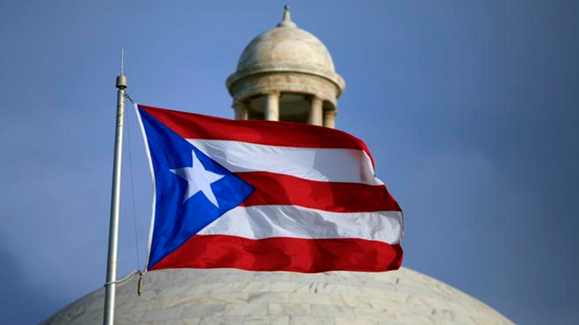FILE - In this July 29, file 2015 photo, the Puerto Rican flag flies in front of Puerto Rico's Capitol as in San Juan, Puerto Rico. Congress edged closer to delivering relief to debt-stricken Puerto Rico as the Senate on Wednesday, June 29, 2016, cleared the way for passage of a last-minute financial rescue package for the territory of 3.5 million Americans. (AP Photo/Ricardo Arduengo, File)