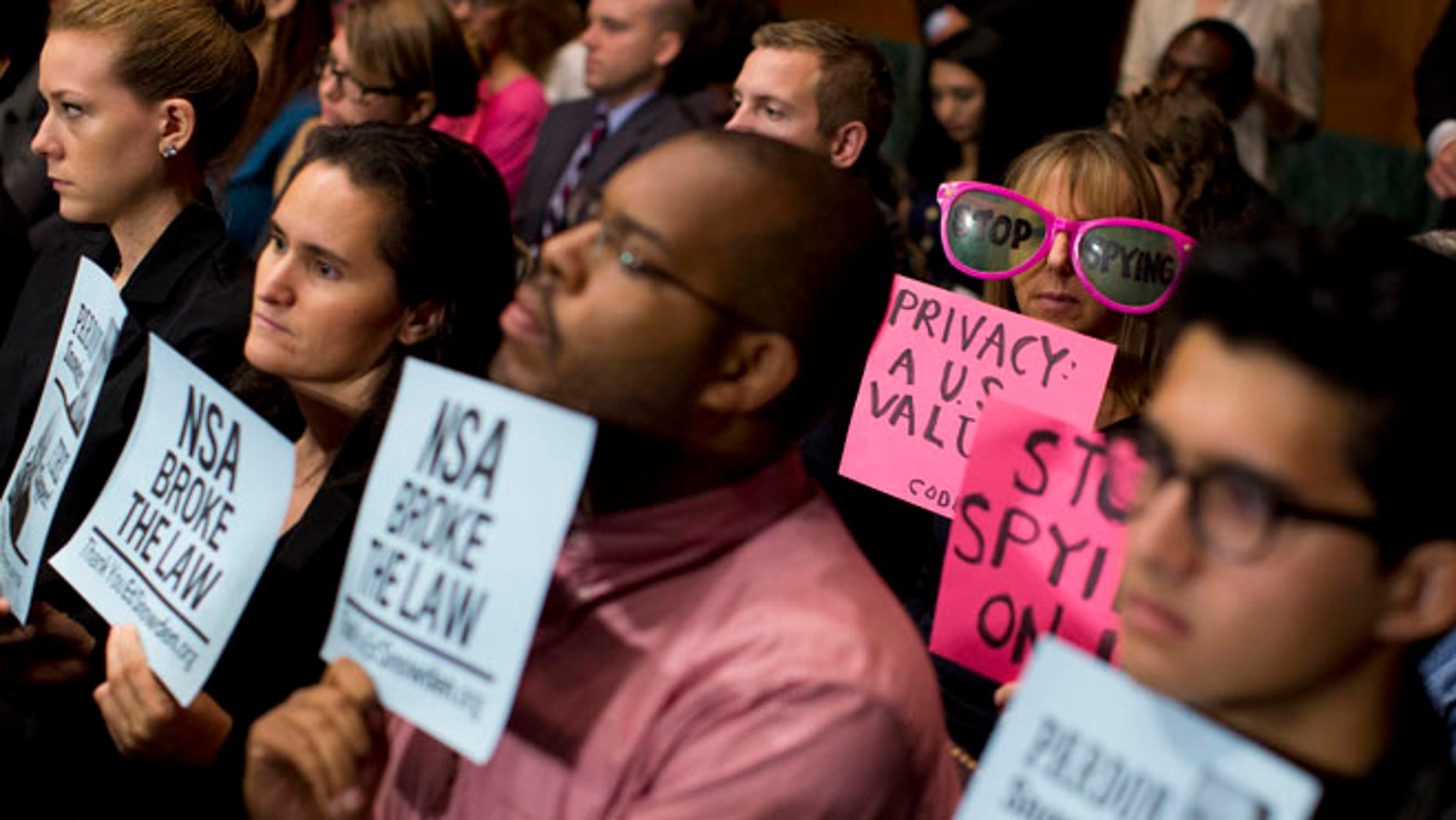 FILE: Oct. 2, 2013: Protestors hold signs, and CodePink founder Medea Benjamin wears oversized sunglasses during a Senate hearing on the Foreign Intelligence Surveillance Act.