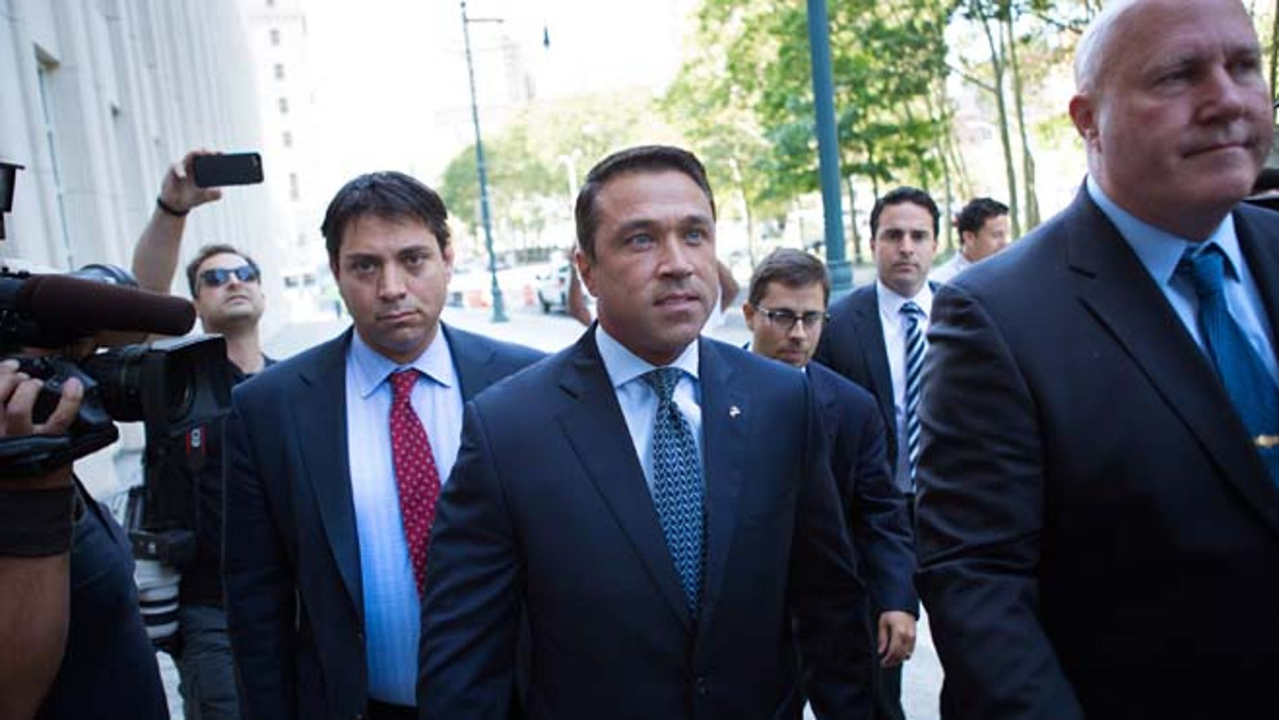 Former U.S. Rep. Michael Grimm, center, arrives ahead of his sentencing at federal court Friday, July 17, 2015, in the Brooklyn borough of New York.  Grimm pleaded guilty late last year to aiding in filing a false tax return, a charge that stemmed from an investigation into the Staten Island Republican's campaign financing. (AP Photo/Kevin Hagen)