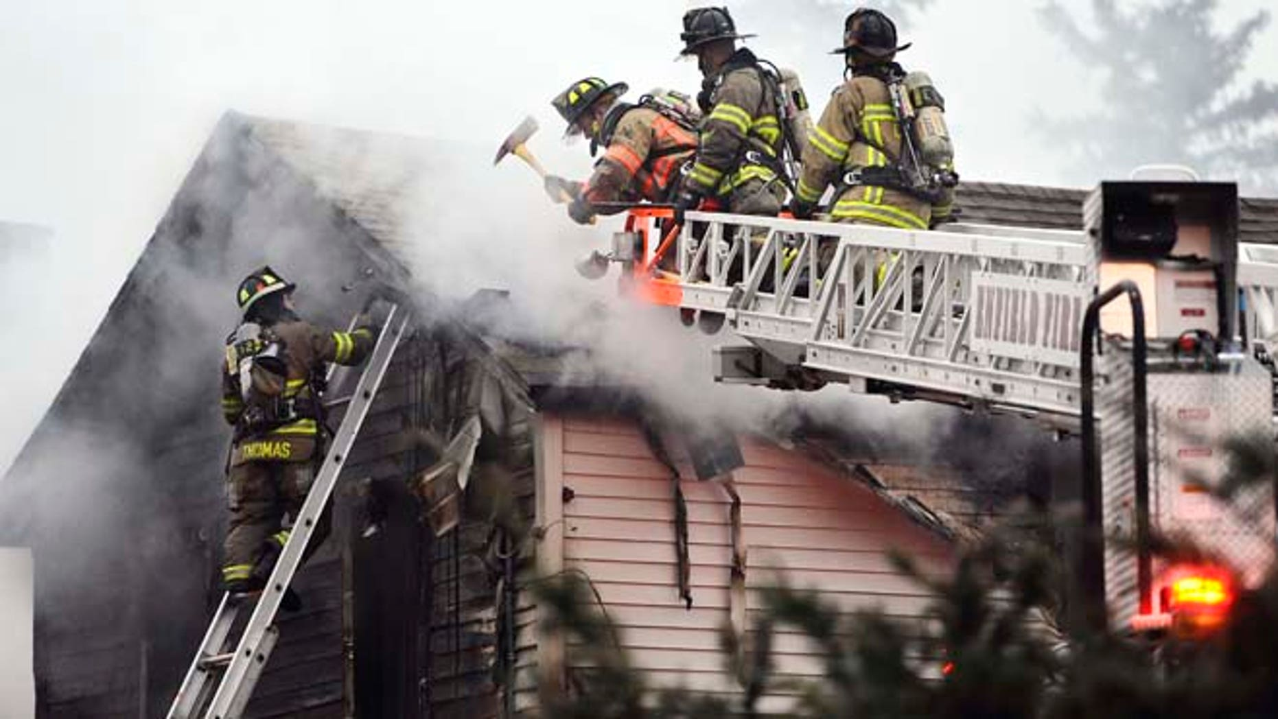 Firefighters control a house fire where  fire officials said four people were reportedly unaccounted for, Wednesday, Dec. 10, 2014, in Enfield, Conn., about 20 miles northeast of Hartford. (AP Photo/Journal Inquirer, Jessica Hill) MANDATORY CREDI