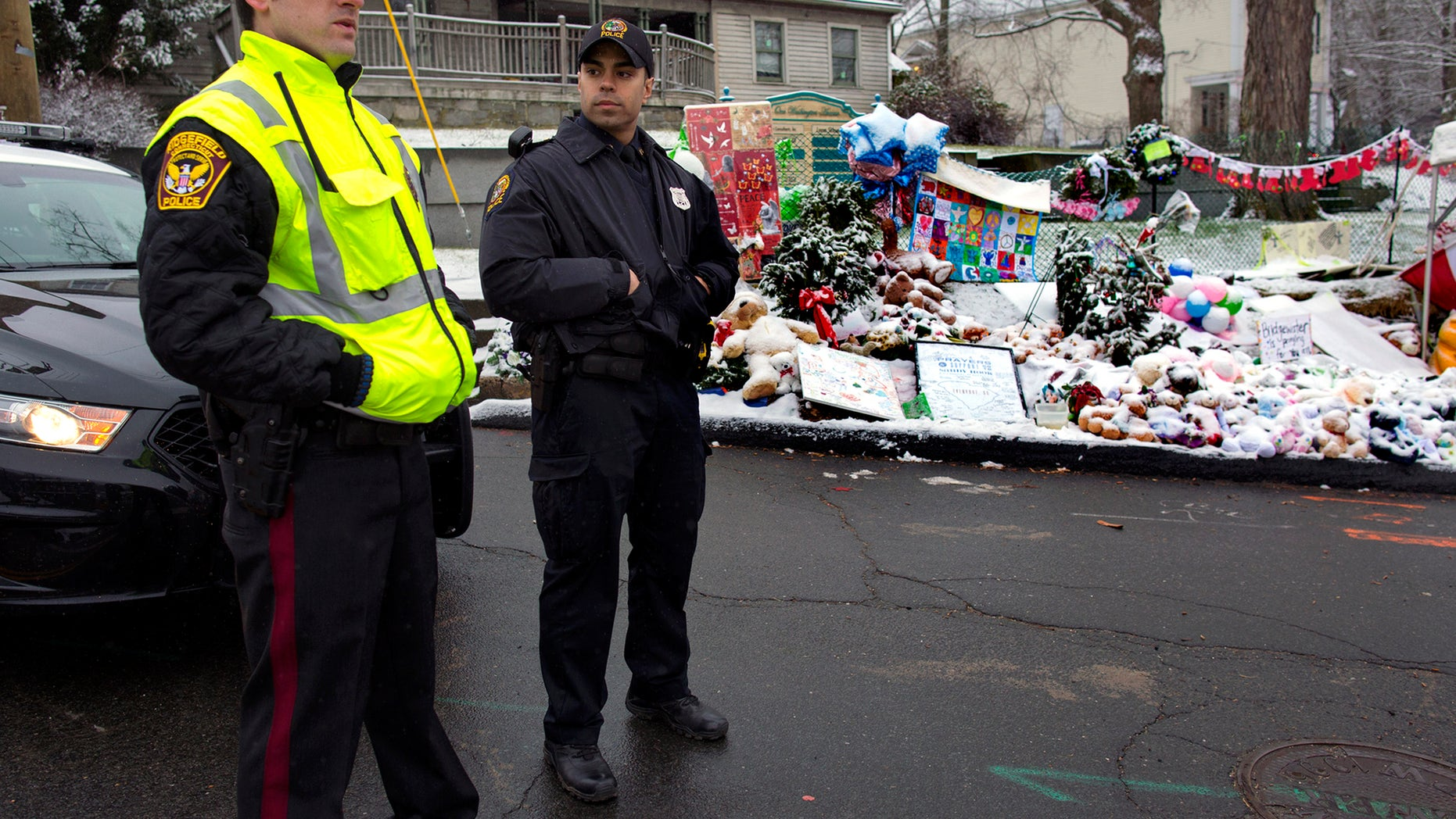 Dec. 25, 2012: From left, Town of Ridgefield, Conn., Det. Durling, and Town of Greenwich, Conn., Officer Rivera stand near a memorial in Newtown, Conn. Regional police agencies arrived in Newtown to relieve the local police force for the Christmas holiday.