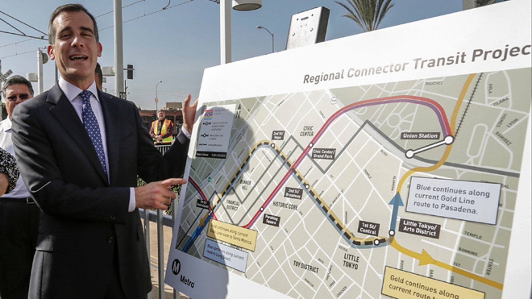 """Los Angeles Mayor Eric Garcetti looks at the proposed """"Regional Connector Transit Project"""" plan as he attends a federal grant signing ceremony in Los Angeles Thursday, Feb. 20, 2014. The light rail public transit system in Los Angeles is getting $670 million to solve one of its most vexing design deficiencies: Train riders who want to travel from one side of downtown and out the other must transfer twice. The """"regional connector,"""" as the Los Angeles County Metropolitan Transportation Authority calls it, will tie together three existing light rail lines with a new tunnel and three new stations. Major construction should begin later this year, with a cost estimated of $1.4 billion, to be opened in 2020. (AP Photo/Damian Dovarganes)"""