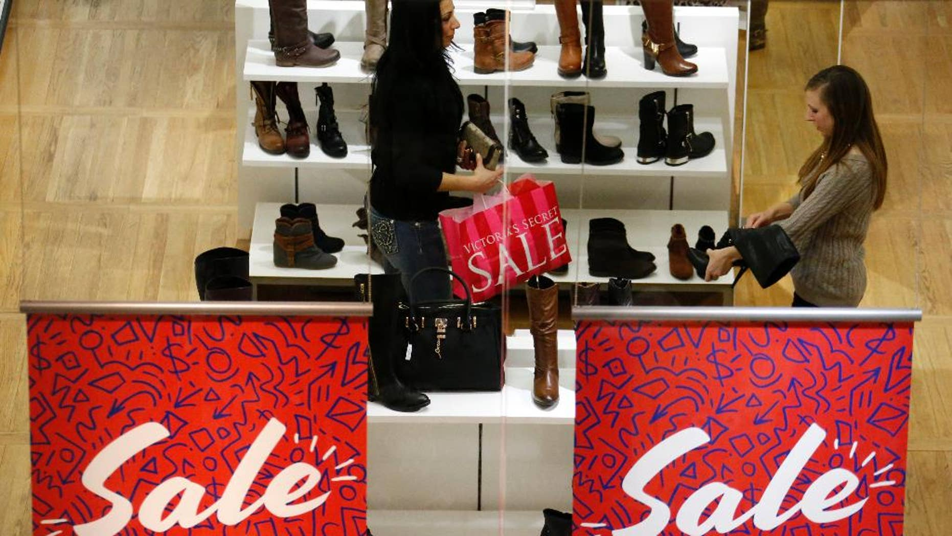 In this Monday, Jan. 13, 2014, photo, shoppers check out the sale at an ALDO store in the Mall at Robinson, in Robinson Township, Pa. The Fedral Reserve releases consumer credit data for January on Friday, March 7, 2014.  (AP Photo/Gene J. Puskar)