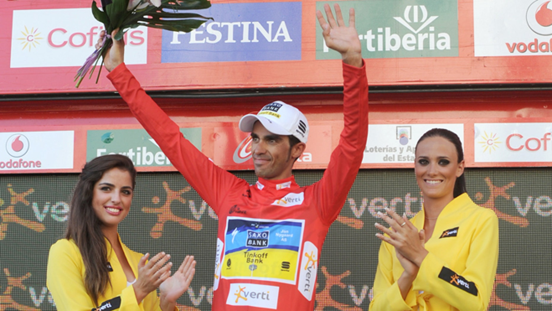 Spanish cyclist Alberto Contador from the Saxo Bank Team celebrates on the podium with the overall red leader jersey at the end  of the 18th stage of the Spanish Vuelta cycling race from Aguilar de Campo to Valladolid, Spain, Thursday, Sept. 6, 2012. The 21-stage, three week race ends in Madrid on Sept. 9. (AP Photo/Israel L.Murillo)