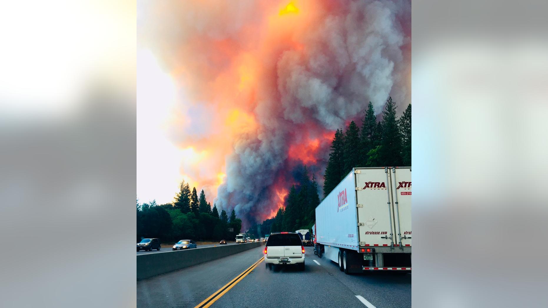 A fire rages as motorists travel on Interstate 5 near Lake Shasta, Calif., Wednesday, Sept. 5, 2018. (Jerri Tubbs via AP)
