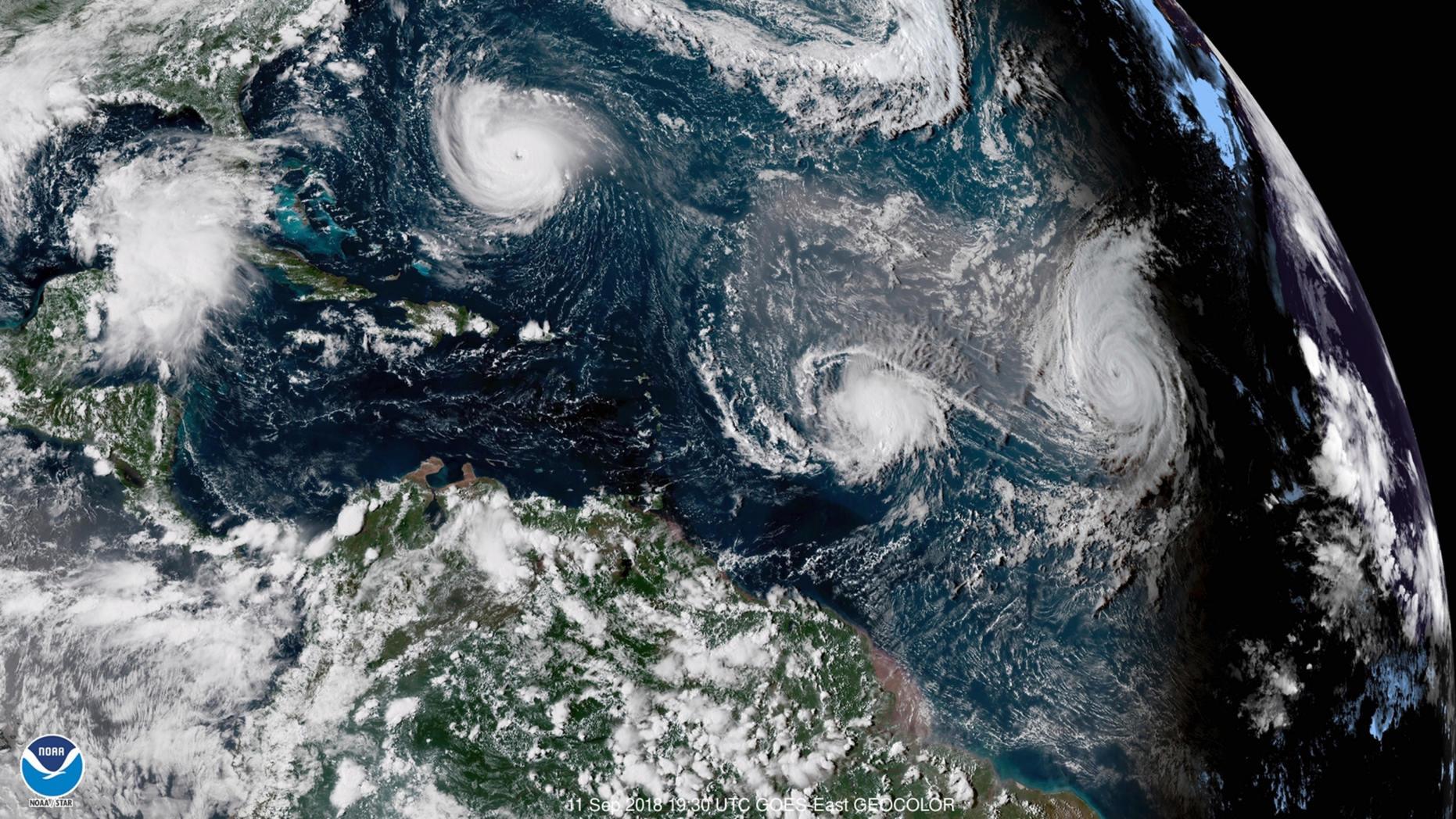 CORRECTS DATE TO SEPT. 11, NOT 1 - This enhanced satellite image made available by NOAA shows Tropical Storm Florence, upper left, in the Atlantic Ocean on Tuesday, Sept. 11, 2018 at 3:30 p.m. EDT. At center is Tropical Storm Isaac and at right is Hurricane Helene. (NOAA via AP)