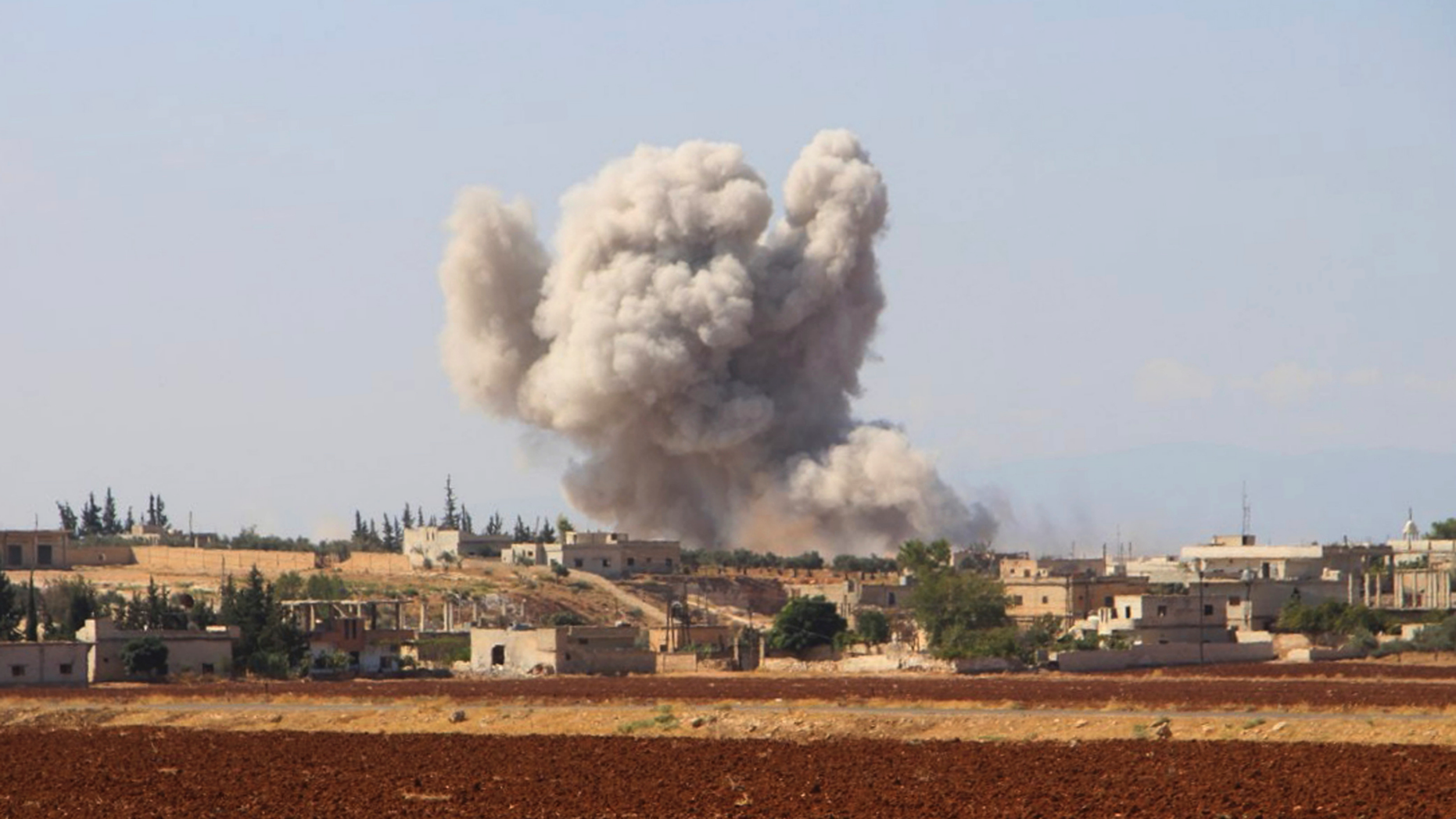 FILE - This file photo released on Monday, Sept 10, 2018 by the Syrian Civil Defense group known as the White Helmets, shows smoke rising from a Syrian government airstrike, in Hobeit village, near Idlib, Syria. As the decisive battle for Idlib looms, a motley crew of tens of thousands of Syrian opposition fighters, including some of the world's most radical, are digging their heels_ looking for ways to salvage what is possible of an armed rebellion that at one point in the seven-year conflict controlled more than half of the country. (Syrian Civil Defense White Helmets via AP, File)