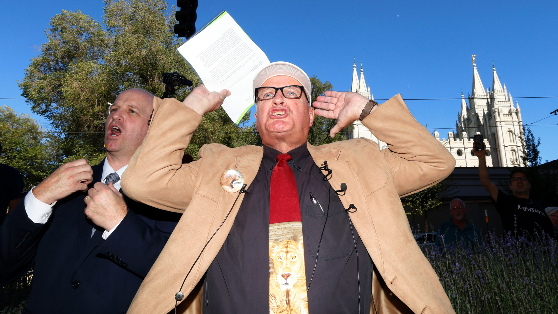 Sam Young reacts after reading a letter detailing his excommunication proceedings from the Mormon Church during a news conference Sunday, Sept. 16, 2018, near Temple Square, in Salt Lake City. Young, a Mormon man who led a campaign criticizing the church's practice of allowing closed-door, one-on-one interviews of youth by lay leaders has been kicked out of the faith. Young, a 65-year-old lifelong Mormon, becomes the third high-profile member of the faith who led protests about church policy to be excommunicated in recent years. (AP Photo/Rick Bowmer)