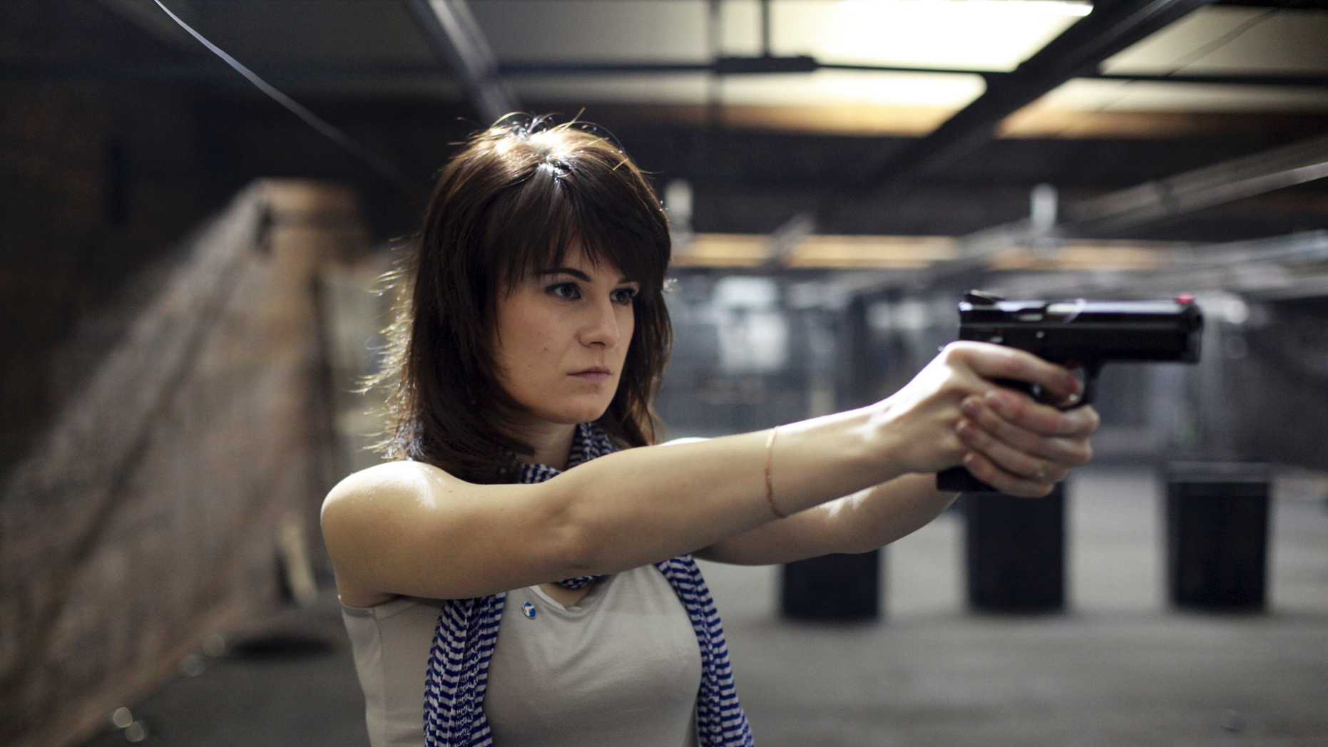 FILE- In this file photo dated Sunday, April 22, 2012, Maria Butina, a gun-rights activist poses for a photo at a shooting range in Moscow, Russia. Russian woman Maria Butina has been jailed in the U.S. on charges that she tried to infiltrate U.S. political organizations as a covert Russian agent, and her father, Valery Butin, told Rossiya TV on Friday Sept. 21, 2018, that the U.S. authorities have eased her prison regime, that jeopardized her health. (AP Photo/Pavel Ptitsin, File)