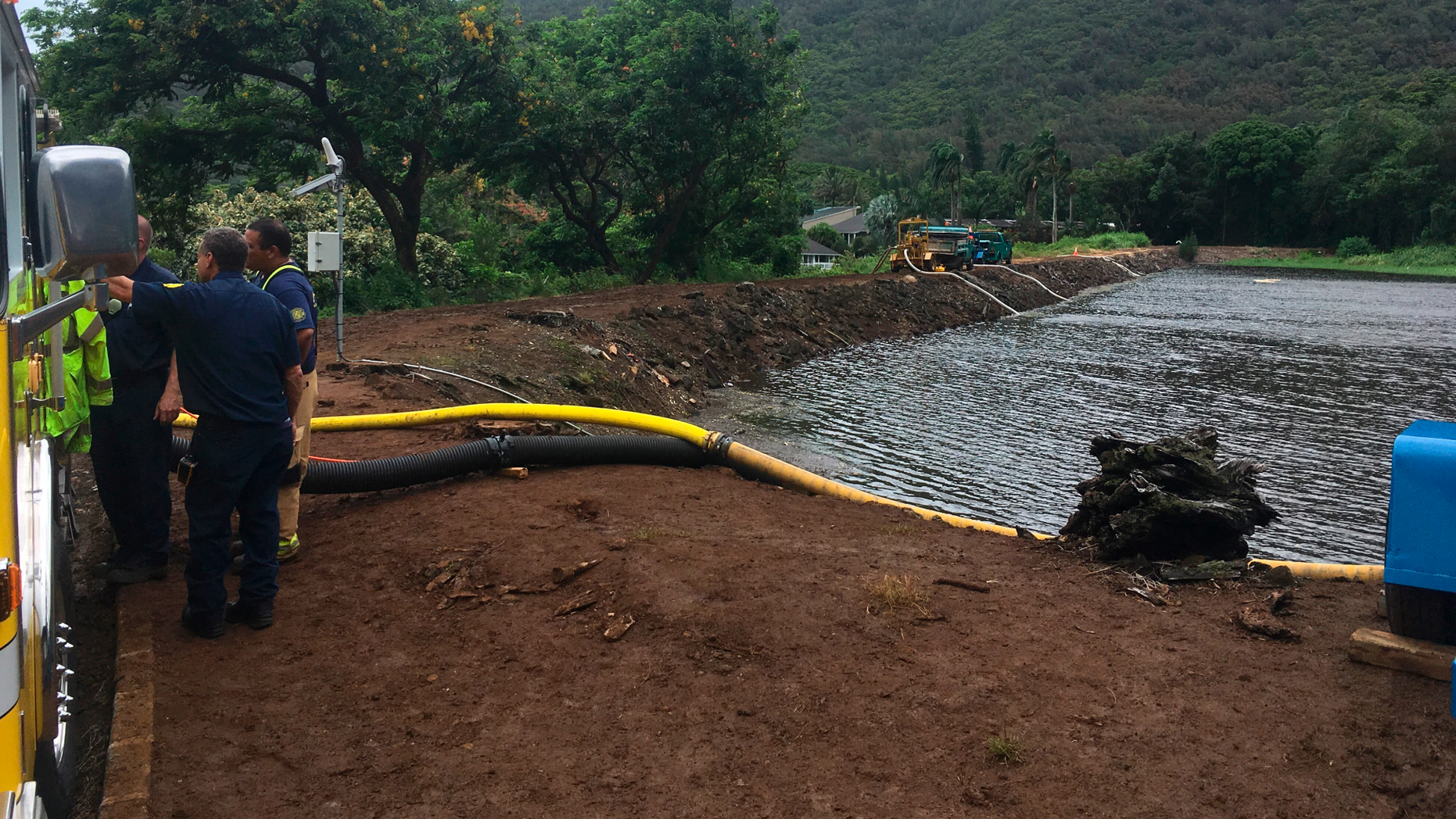 Officials pump water from a reservoir where a dam came close to overflowing in Honolulu on Thursday, Sept. 13, 2018. Honolulu officials say they may need to evacuate 10,000 people from a residential neighborhood if water in the reservoir continues to rise after heavy rains from a tropical storm. (AP Photo/Caleb Jones)