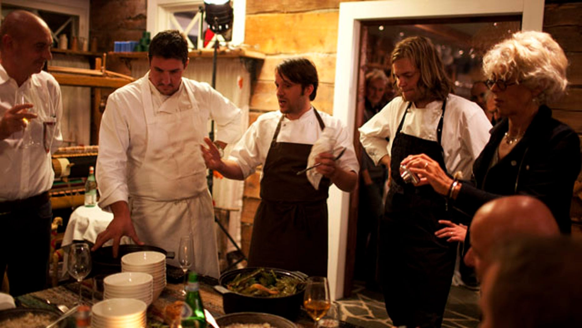 """In this September 2010 photo released by Cook It Raw shows Rene Redzepi, and his team presenting the final dish on the last evening during """"Cook It Raw"""" in Lapland, Finland. The event marked the third time in just over a year that this international group of chefs have hunted, fished and foraged together in a particular location, then prepared a meal while leaving the smallest possible footprint on the environment. (AP)"""