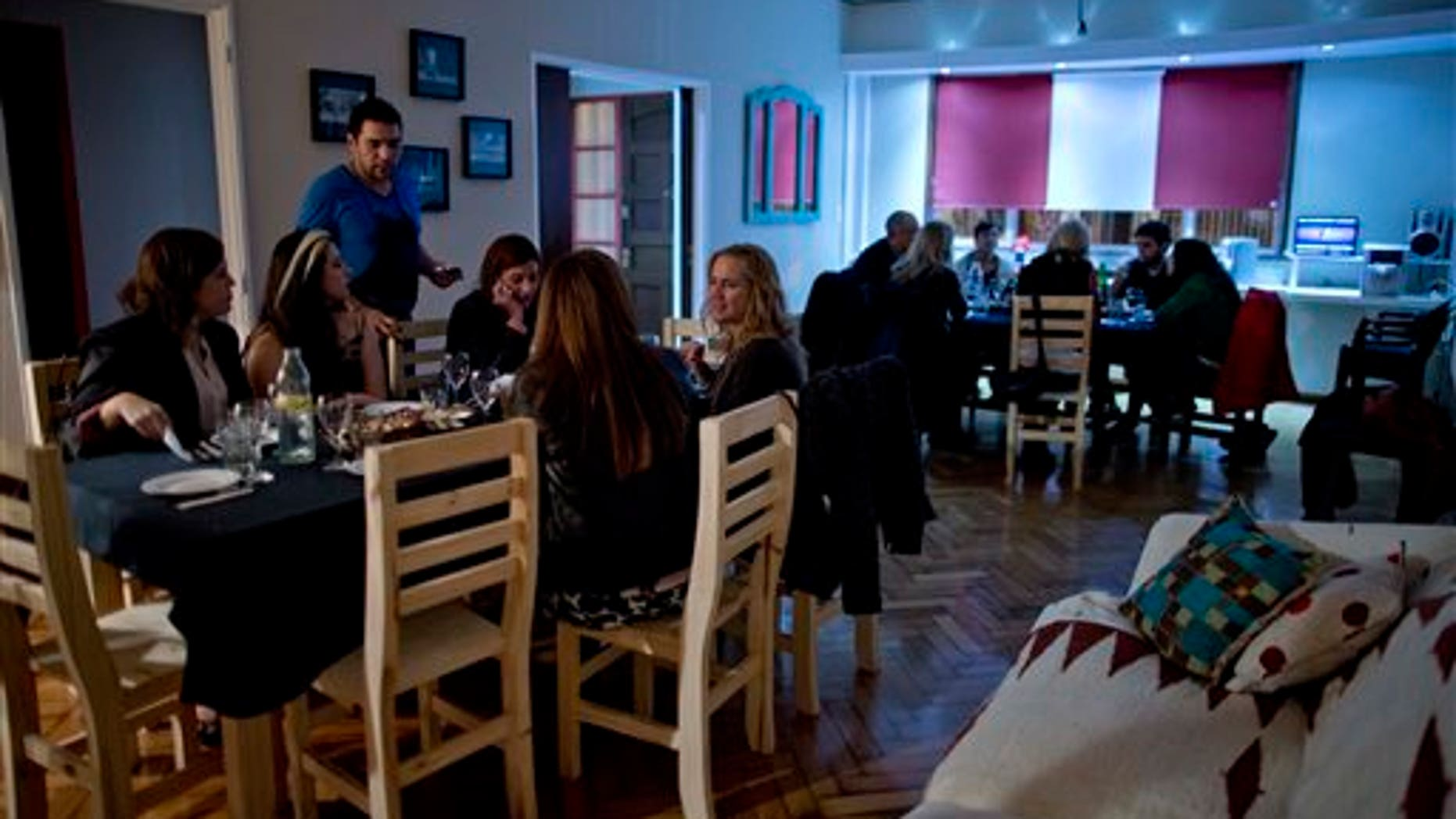 In this April 12, 2014, photo, Chef Ezequiel De La Torre, left top, talks to customers in Buenos Aires, Argentina. The website www.cookapp.com was launched in March 2013 and recently moved its headquarters from Buenos Aires to New York City. It works like a matchmaker, arranging intimate gourmet dinners between strangers. Chefs list when and where they will prepare particular meals; diners book what interests them, pay upfront via the app, then just show up and enjoy.  (AP Photo/Natacha Pisarenko)