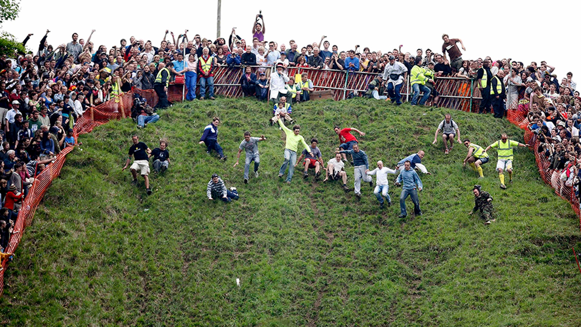 The annual Cooper's Hill Cheese Roll in Brockworth, England, draws hundreds of spectators eager to watch people hurl themselves down the steep hill after wheels of cheese.