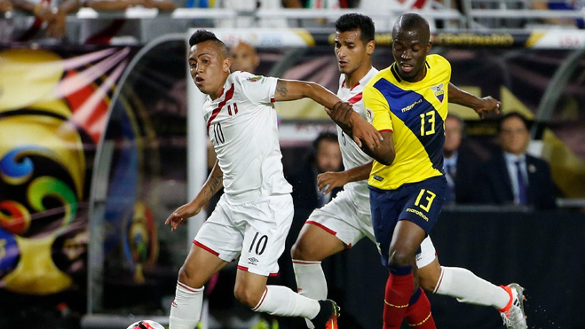 Peru's Christian Cueva dribbles the ball away from Ecuador's Enner Valencia on June 8, 2016, in Glendale, Ariz.