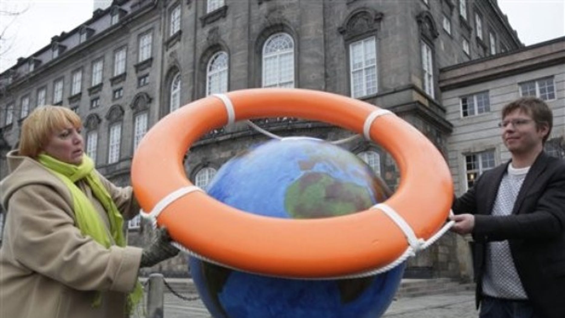 Claudia Roth, left, leader of the German Green Party, and Jakob Norhoj, right, of the Danish Socialist people's party, put a lifebuoy around planet earth outside parliament, rear, in Copenhagen Friday Dec. 11, 2009.