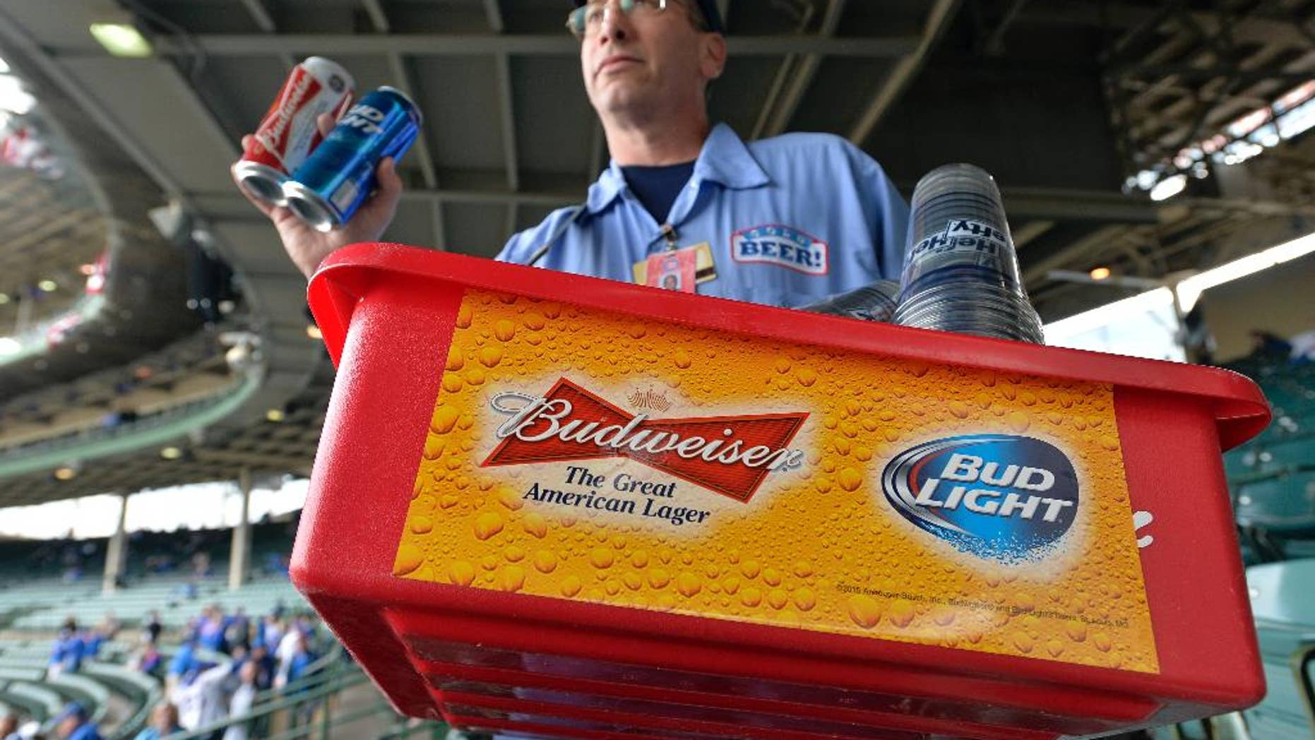 FILE - In this Tuesday, Oct. 13, 2015, file photo, a beer vender holds up Budweiser and Bud Light at Wrigley Field before Game 4 in baseball's National League Division Series between the Chicago Cubs and the St. Louis Cardinals in Chicago. Budweiser's owner Anheuser Busch InBev clinched a preliminary deal earlier this month to take over British beer company SABMiller for around 69 billion pounds ($106 billion). A survey from consulting firm EY on Monday, Oct. 26, 2015, points to more global mega-deals in the year to come. (AP Photo/Paul Beaty, File)