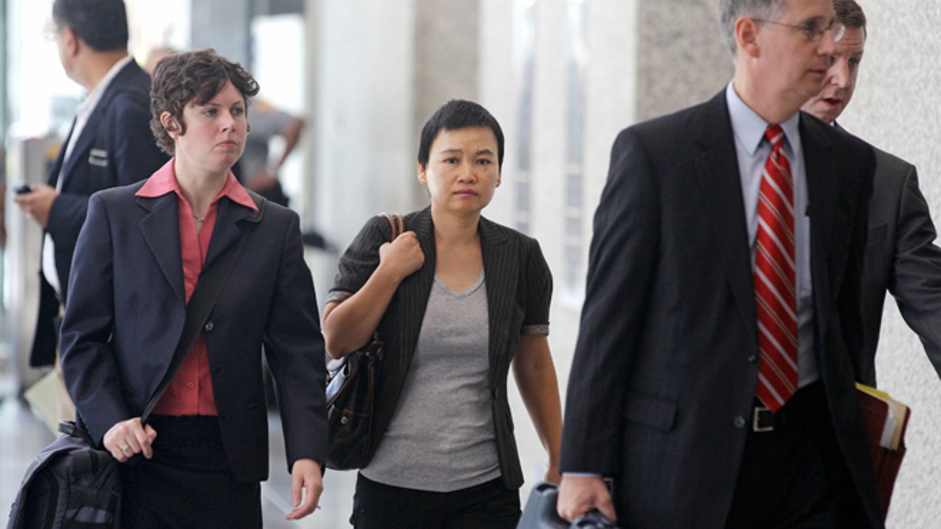 Aug. 29, 2012: Hanjuan Jin, center, leaves a federal courthouse in Chicago after being sentenced to four years in prison for stealing trade secrets from Motorola.