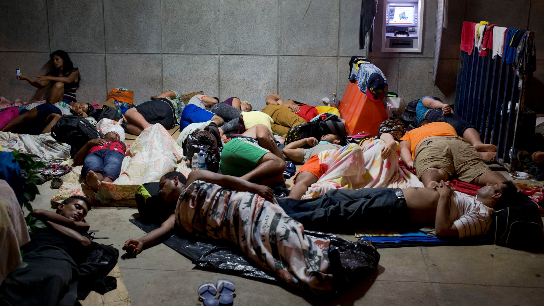 In this Saturday, Nov. 21, 2015 photo, a Cuban woman migrant uses her cell phone while other Cubans sleep, outside of the border control building in Penas Blancas, Costa Rica, on the border with Nicaragua. Some 45,000 Cubans will move by bus, boat, taxi and on foot from Ecuador and other South and Central American countries to the Texas and California borders this year, afraid that the normalization of relations between the U.S. and Cuba will mean an imminent end to special immigration privileges that date to the opening of the Cold War. (AP Photo/Esteban Felix)