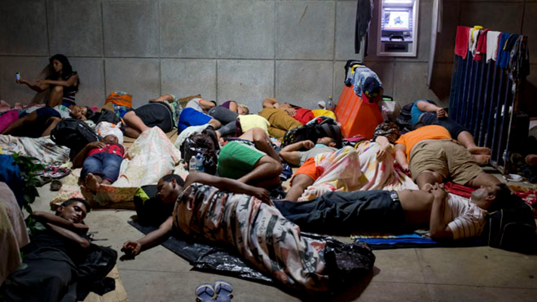 In this Nov. 21, 2015 file photo, a Cuban woman migrant uses her cell phone while other Cubans sleep, outside of the border control building in Penas Blancas, Costa Rica. (AP Photo/Esteban Felix, File)