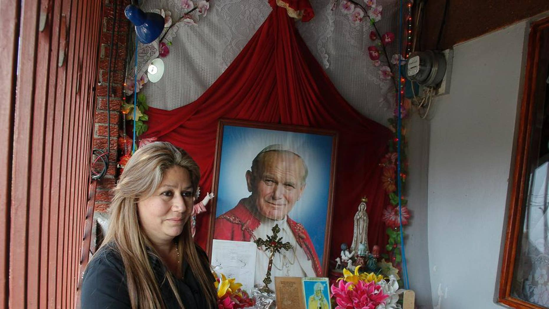 FILE - In this July 5, 2013 file photo, Floribeth Mora stands by her shrine to Pope John Paul II inside the entrance to her home in La Union de Cartago, Costa Rica. Mora, her doctors and the Catholic Church say her aneurysm disappeared in May of 2011 in a miracle that cleared the way for the late pope to be declared a saint. Mora will attend the ceremony at the Vatican on April 27, 2014 as a guest of honor. (AP Photo/Enrique Martinez, File)