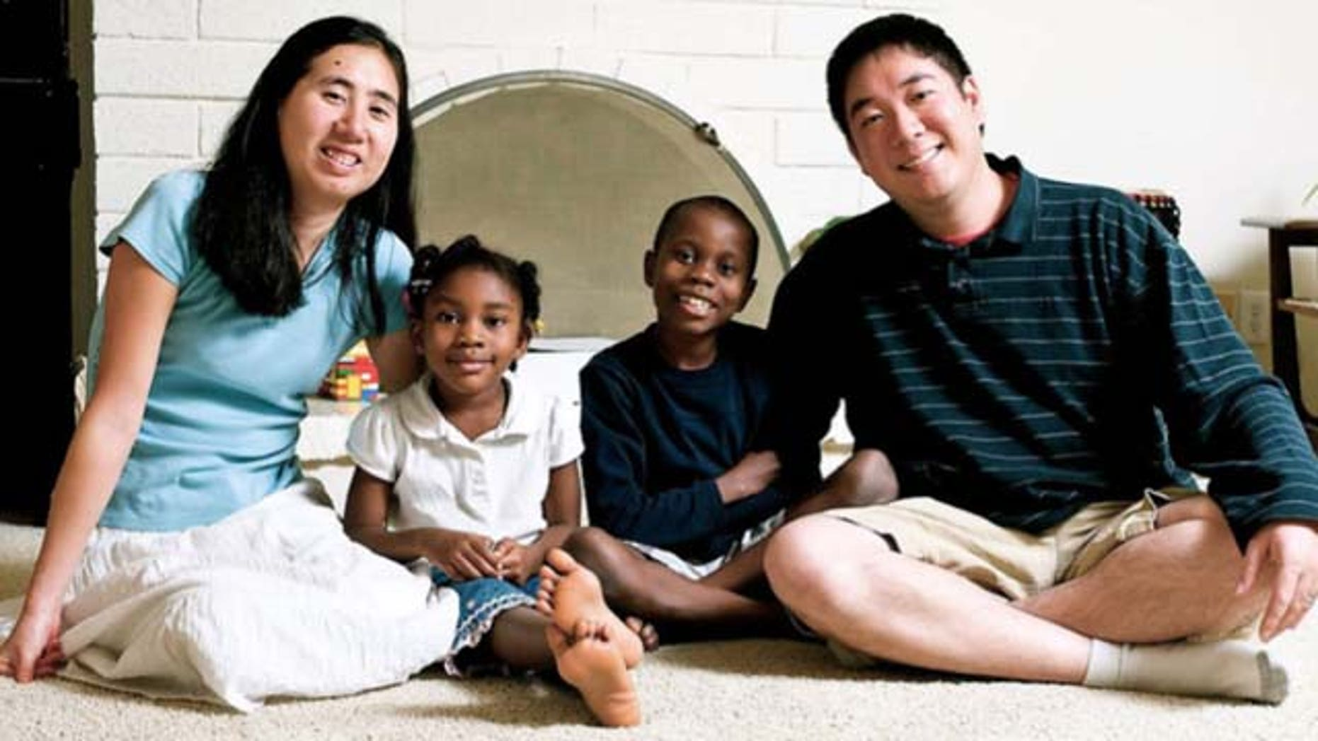 This undated photo provided by the David House Agency shows Matthew, right, and Grace Huang, left, with two of their adopted children, Gloria, center left, and one of their two sons. The couple has been jailed in Qatar on a charge of murder with intent and is accused of starving Gloria, 8, to death, according to a coalition of legal and public relations groups that are working on the case from the U.S. and trying to draw publicity to what they claim is are unjust arrests. (AP Photo/
