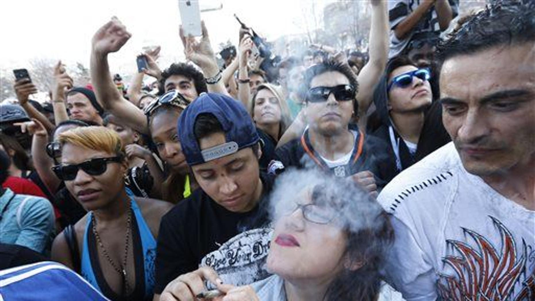 Partygoers listen to live music and smoke pot on the second of two days at the annual 4/20 marijuana festival in Denver, Sunday, April 20, 2014.