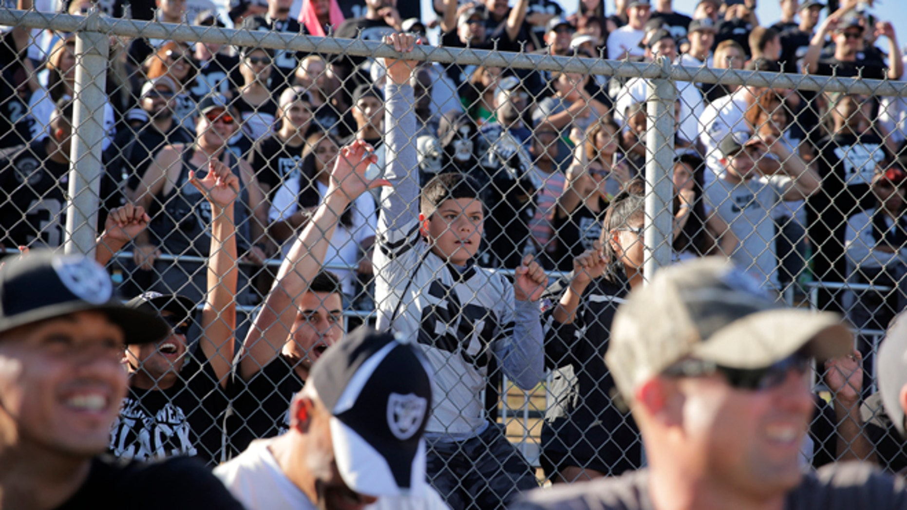 Oakland Raiders fans watch during the team's joint football practice with the Dallas Cowboys on Tuesday, Aug. 12, 2014, in Oxnard, Calif. (AP Photo/Jae C. Hong)