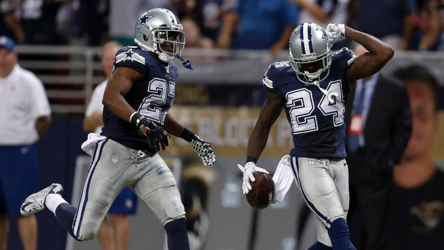 Dallas Cowboys cornerback Morris Claiborne, right, celebrates after intercepting a pass as teammate strong safety J.J. Wilcox watches during the fourth quarter of an NFL football game against the St. Louis Rams, Sunday, Sept. 21, 2014, in St. Louis. The Cowboys won 34-31. (AP Photo/Jeff Roberson)