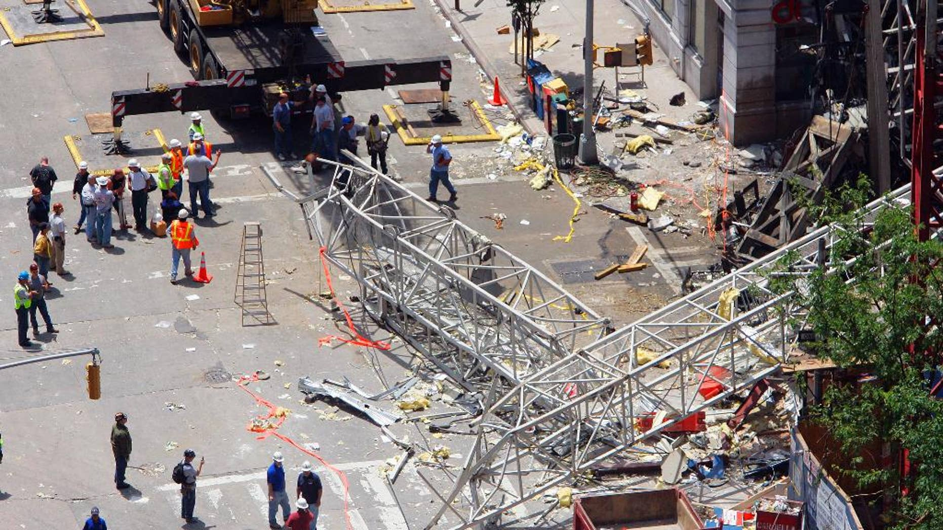 FILE - In this May 30, 2008 file photo, crews work at the scene of a crane collapse on the Upper East Side of New York. The New York City construction crane owner who was acquitted of manslaughter in a collapse that killed two workers has gone on trial again in a civil wrongful death case. Lawyers for the slain workers' families gave opening statements on Friday, May 23, 2014 in the trial of James Lomma, his company and others involved in the accident. (AP Photo/Stephen Chernin, File)