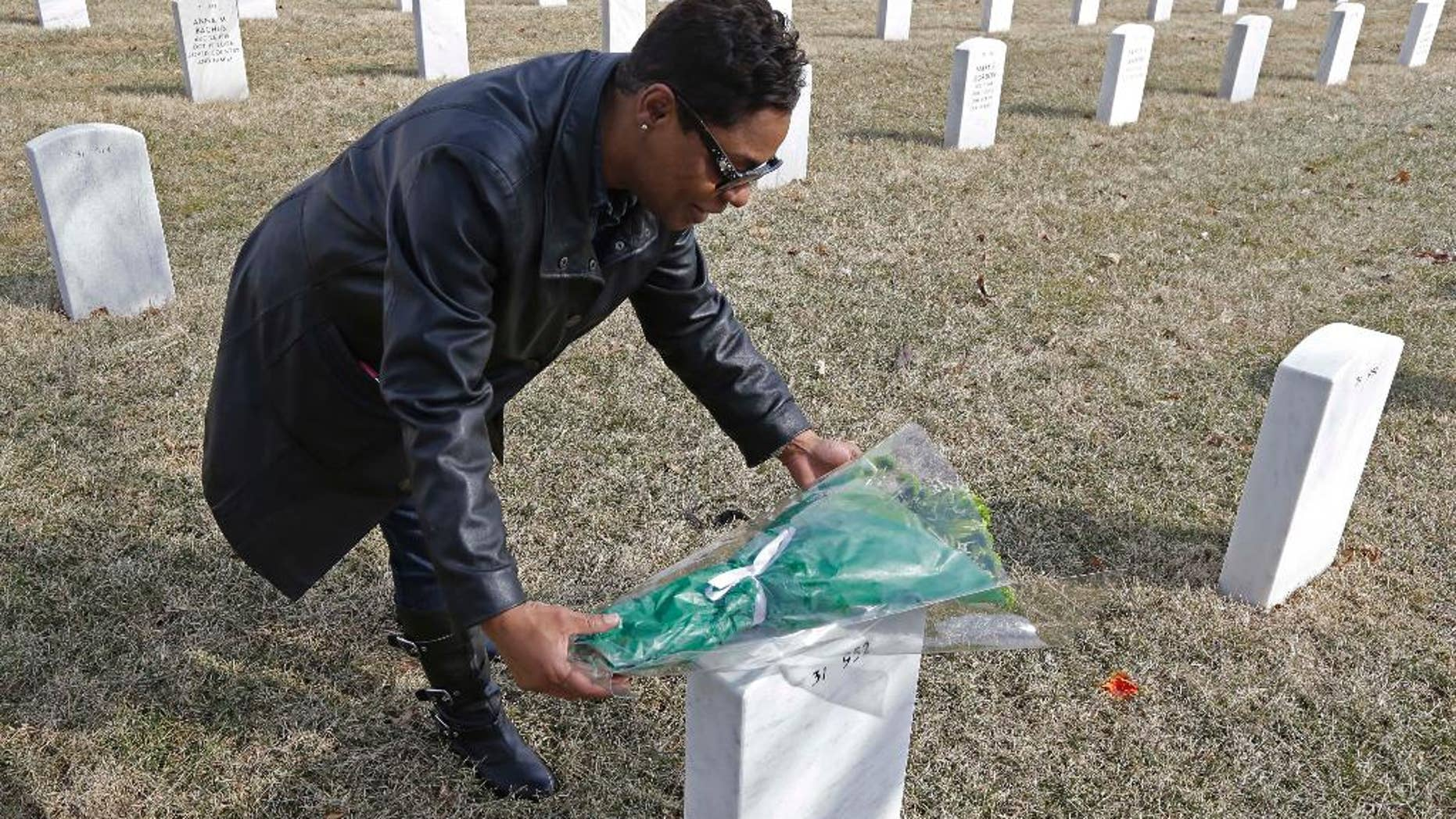 Dellaina Grundy places flowers on her father's headstone, Army veteran Leroy Metcalfe, Saturday, March 8, 2014, at the Dayton National Cemetery in Dayton, Ohio. Grundy isn't sure whether any or all of the cremated remains buried in the grave are his and knows that mystery will never be solved.(AP Photo/Al Behrman)