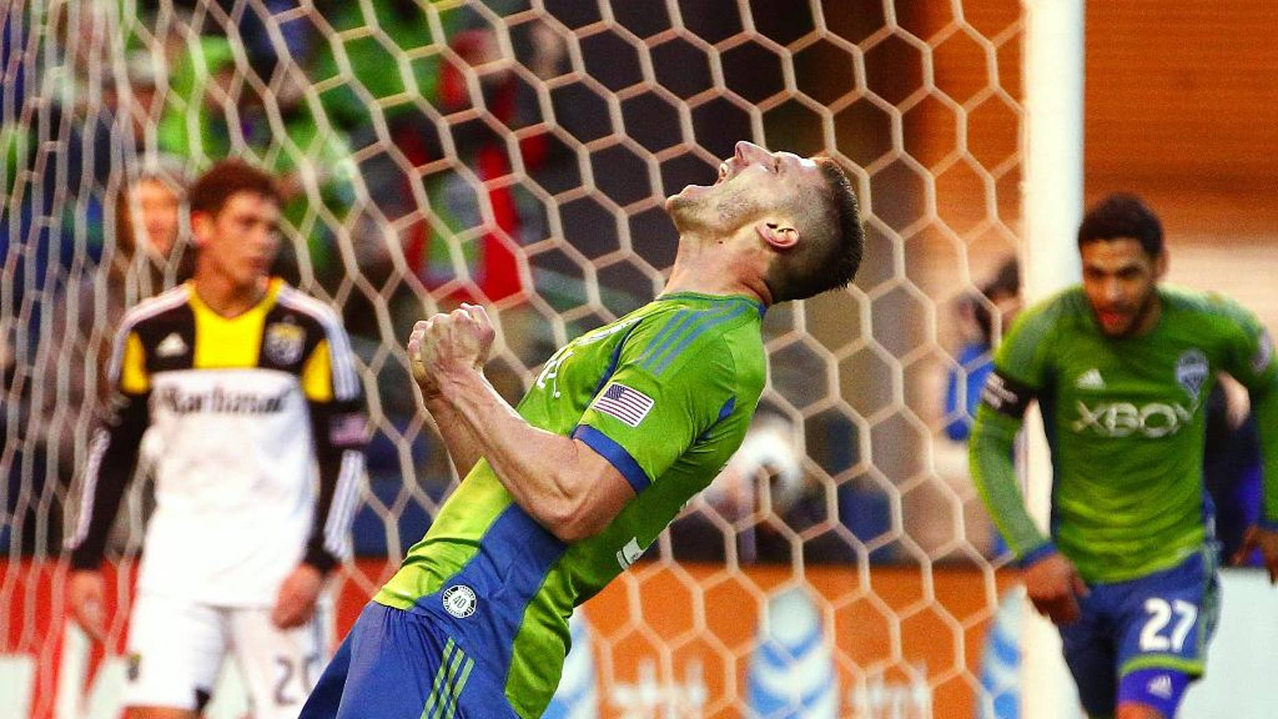 Seattle Sounders midfielder Kenny Cooper celebrates after scoring against Columbus Crew goalkeeper Steve Clark in the first half od an MLS soccer game on Saturday, March 29, 2014, in Seattle, Wash. (AP Photo/The Seattle Times, John Lok) MANDATORY CREDIT TO BOTH THE SEATTLE TIMES AND THE PHOTOGRAPHER; SEATTLE OUT; USA TODAY OUT; MAGAZINES OUT; TV OUT, NO SALES