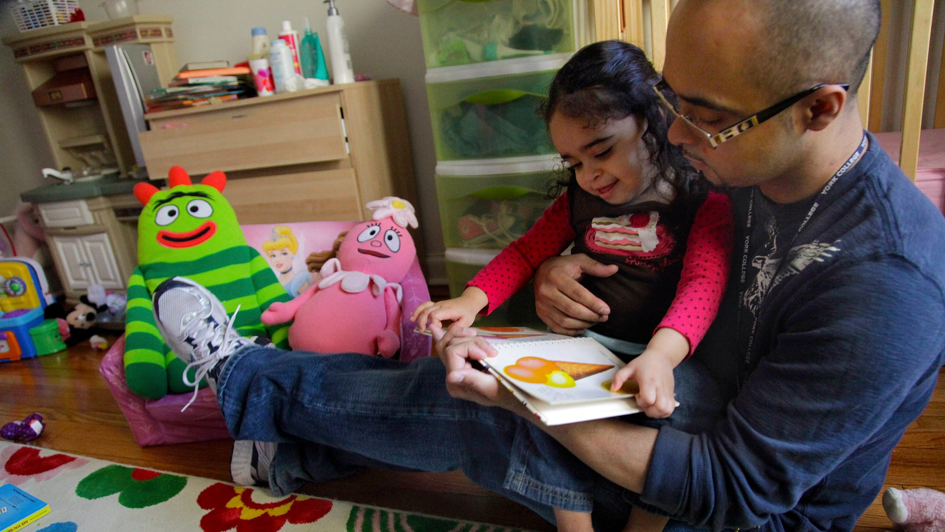 Christopher Astacio reads with his daughter Cristina, 2, recently diagnosed with a mild form of autism. (AP Photo/Bebeto Matthews)